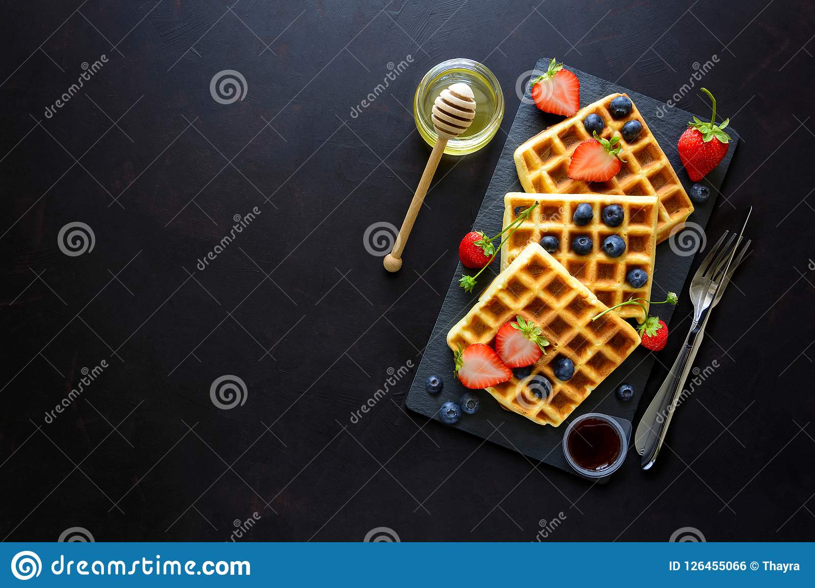 Belgian waffles with strawberries, blueberries and honey on slate plate on dark wooden background. Top view. Copy space