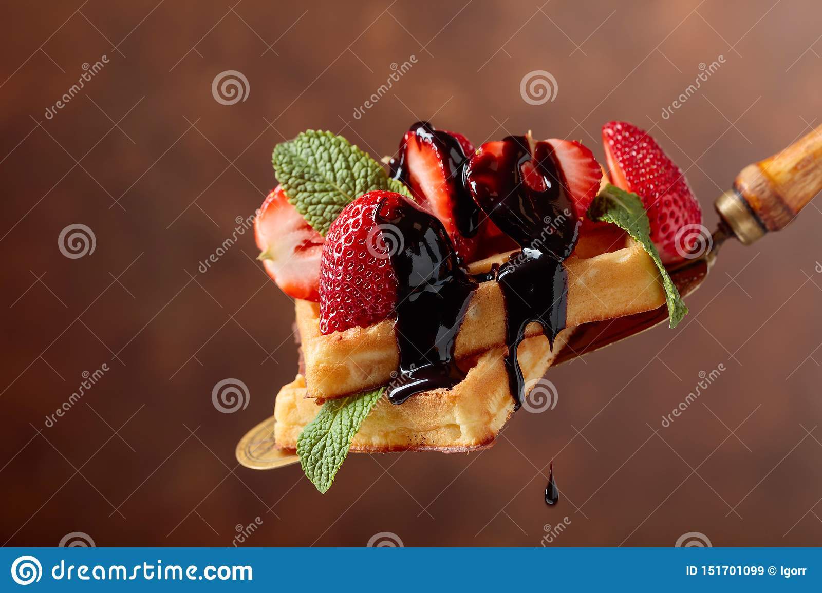 Belgian waffles with strawberries, mint and chocolate sauce