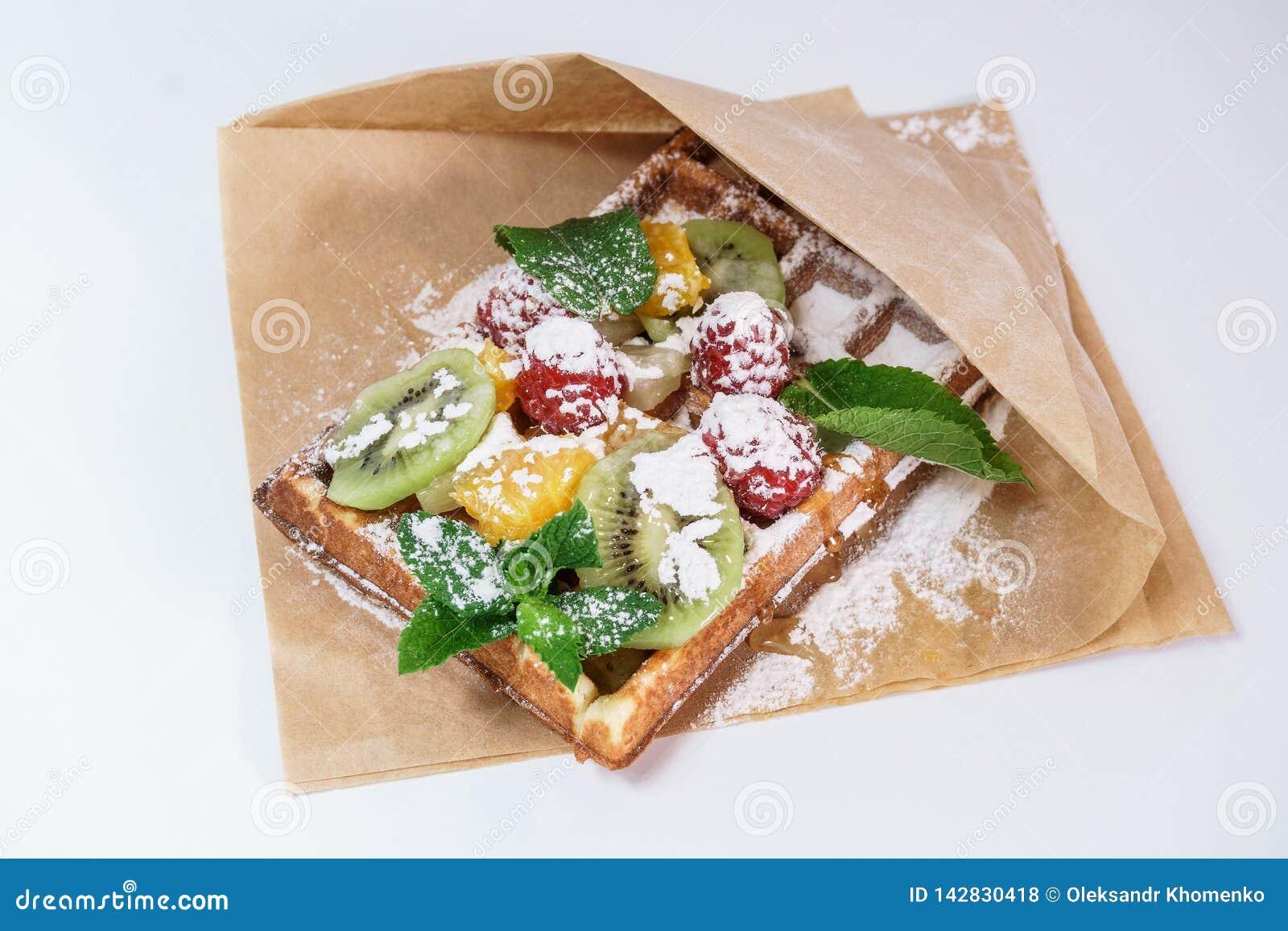 Belgische wafel met fruit en gepoederde suiker op een witte achtergrond
