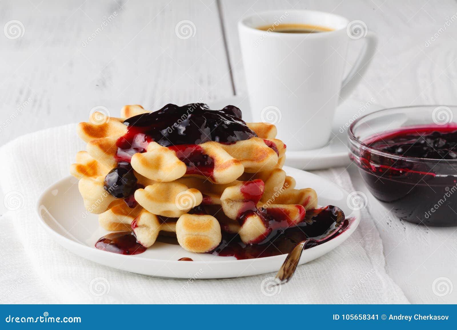 Belgische Waffeln mit creem und berrie stauen auf weißem hölzernem Hintergrund
