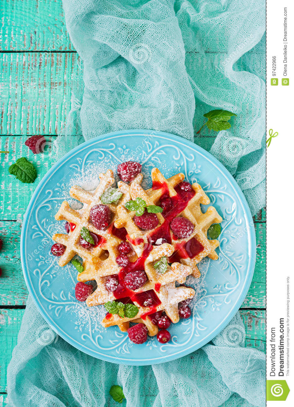 Belgium waffles with raspberries and syrup
