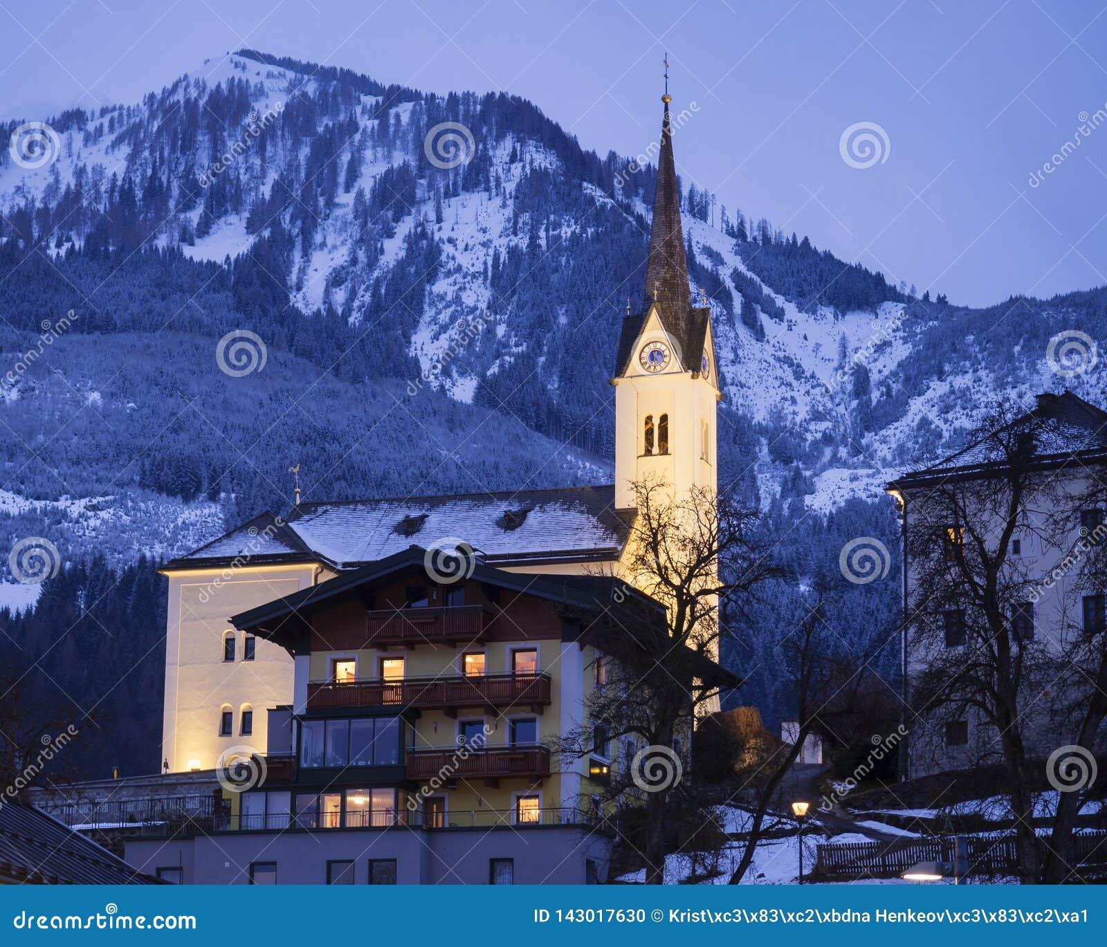 Belichtetes katholische Kirche St. Margaretha mit Straße, Lichtern, Bergen und Wald in Kaprun Österreich an der blauen Stunde