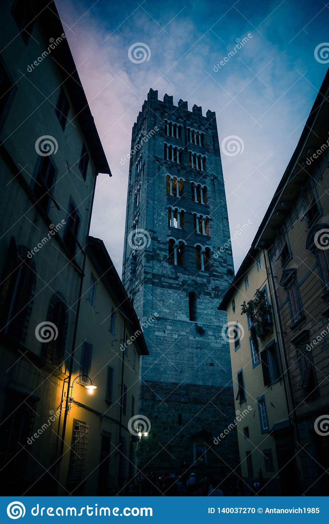 Bell tower of Chiesa di San Frediano catholic church view through narrow street with lamp light in historical centre of old mediev