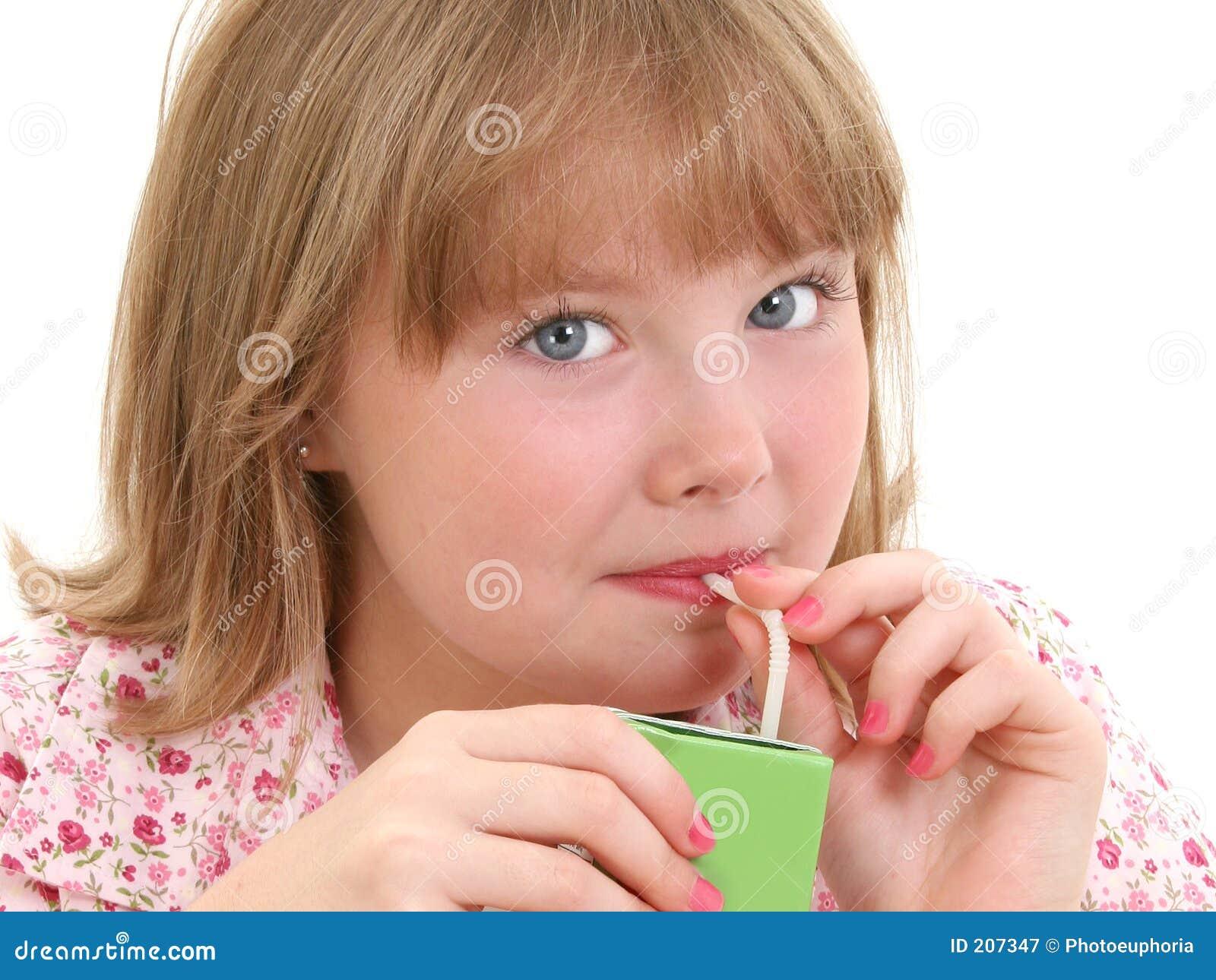 Bella bambina che beve dal contenitore di spremuta