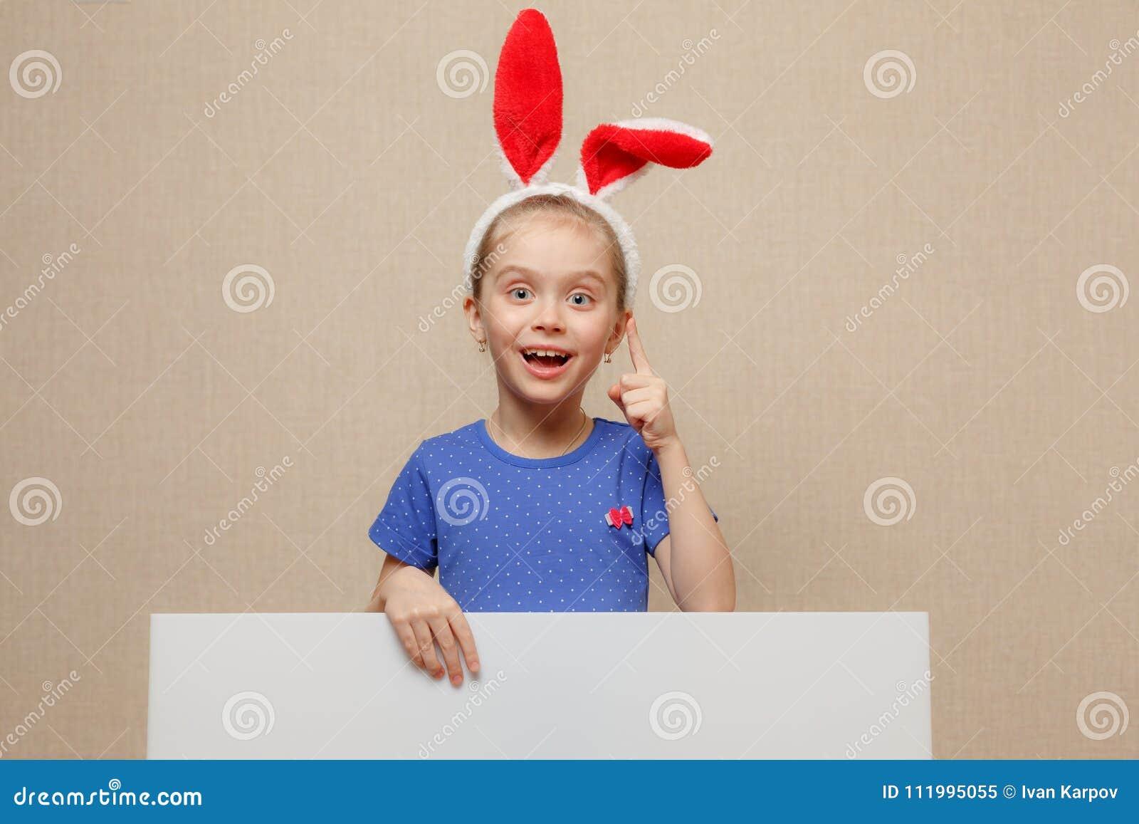 Bella bambina con le orecchie del coniglietto e l insegna in bianco Pasqua felice