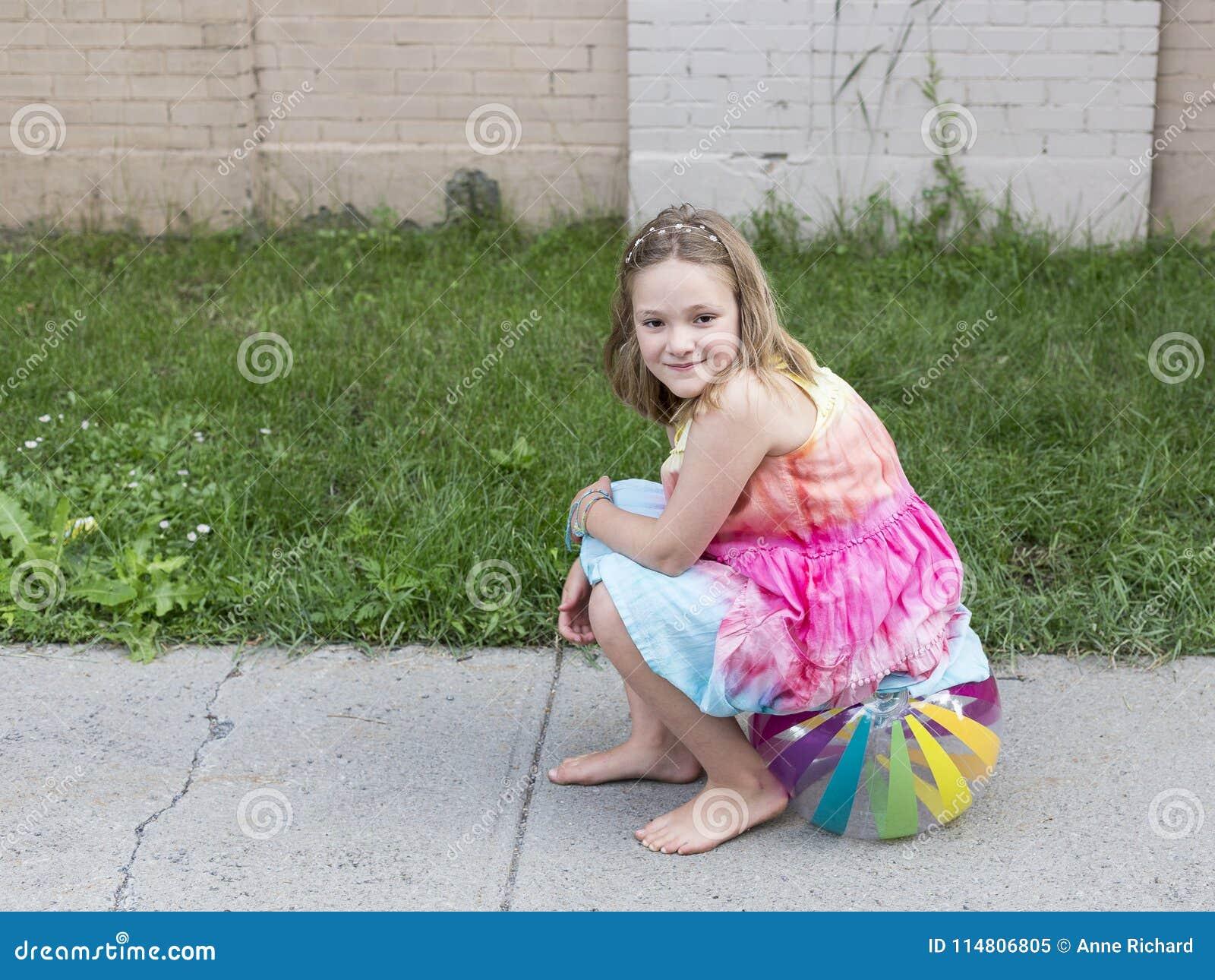 Bella bambina sorridente nel vestito da estate e nei piedi nudi che si siedono sul beach ball sul marciapiede