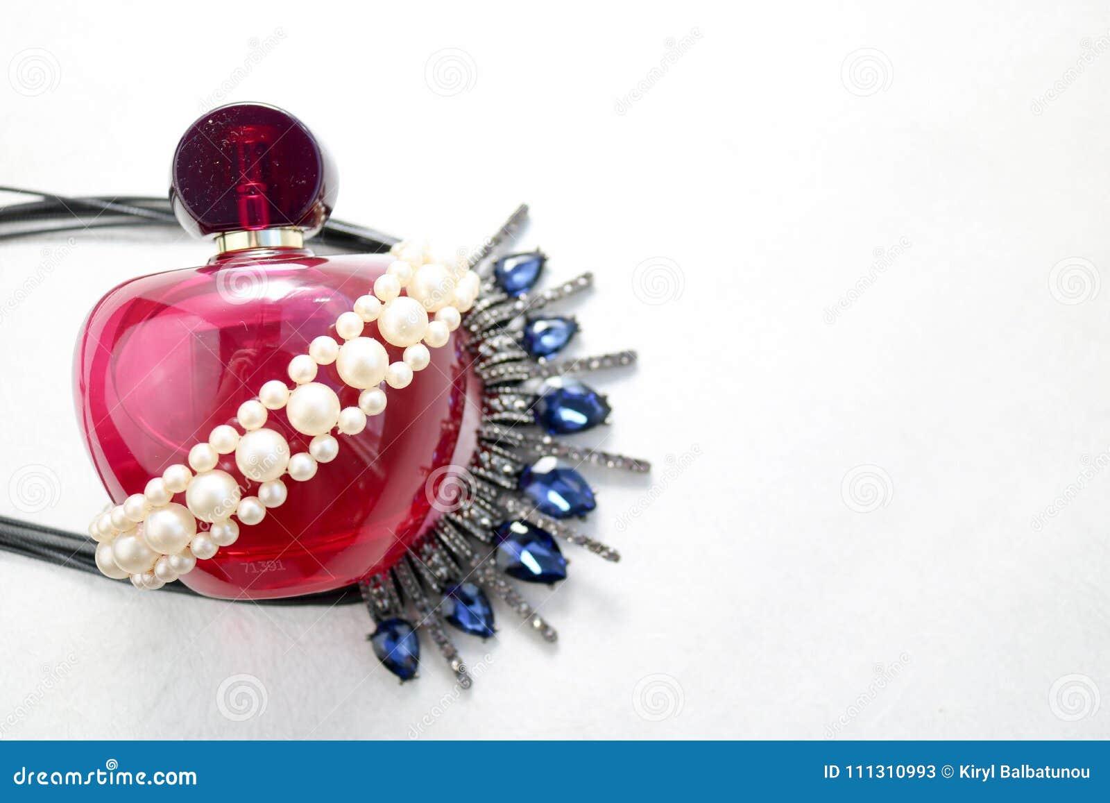 Bella bottiglia trasparente di vetro rosa di profumo femminile decorata con le perle grige bianche ed i diamanti blu e del posto