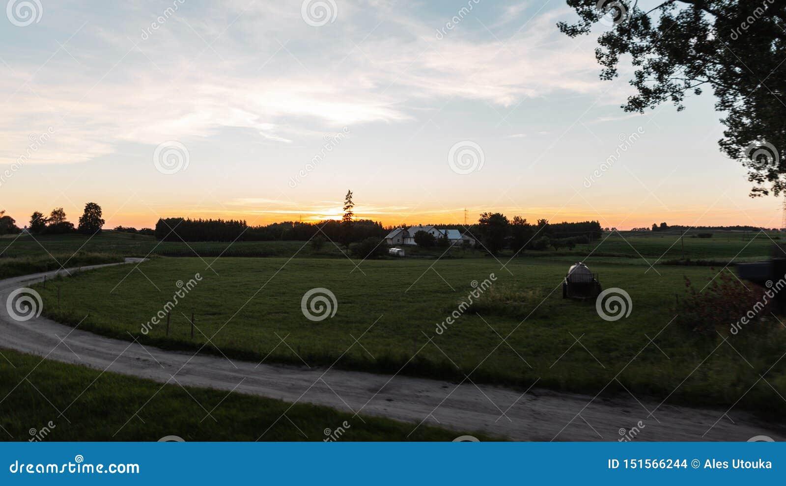 Bella campagna del paesaggio di estate al tramonto Percorso al villaggio Grande casa delle vacanze nella campagna sera