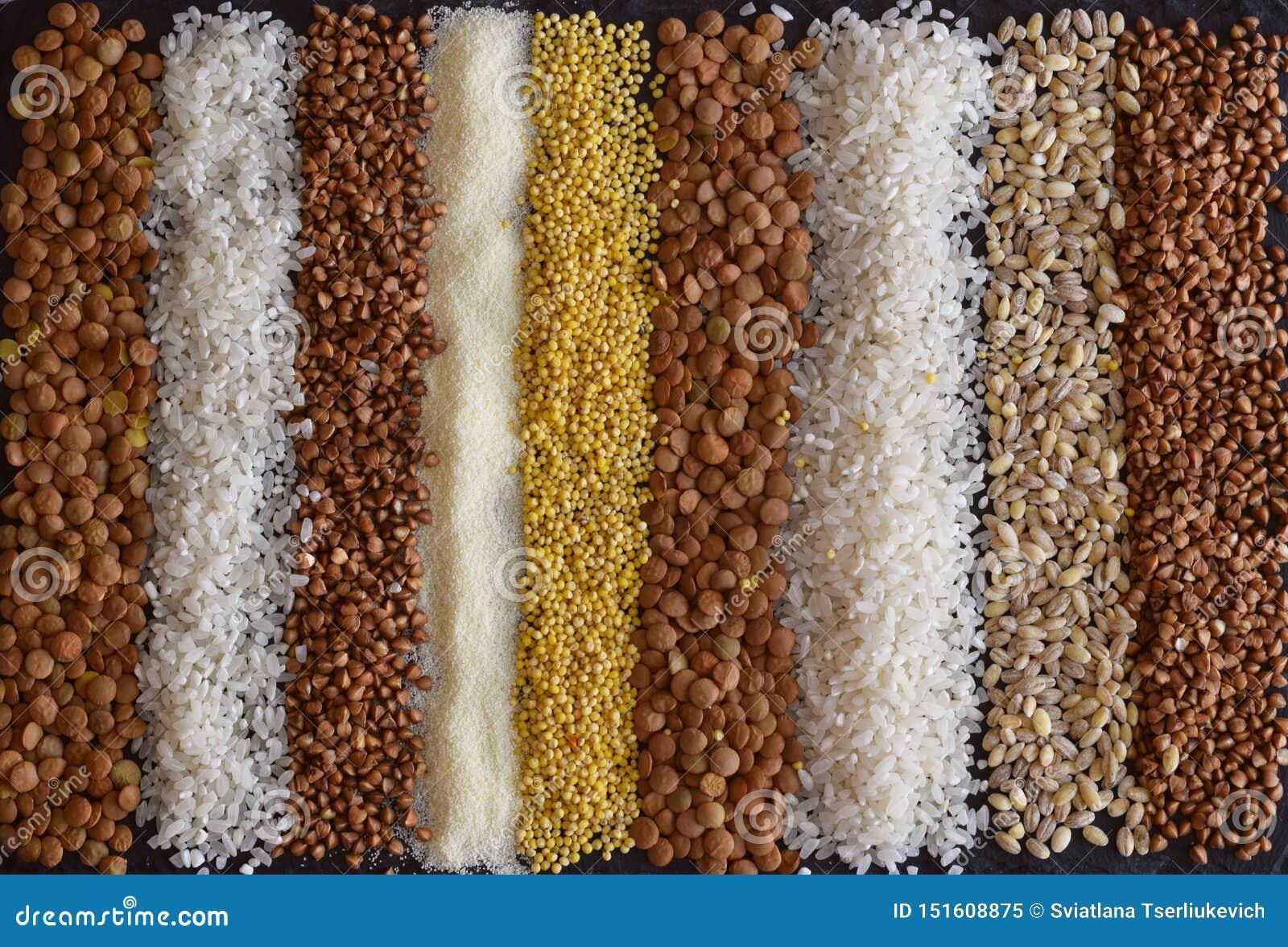 Bella composizione dei grani differenti sulla tavola: grano saraceno, miglio, semolino, lenticchie, orzo perlato, riso