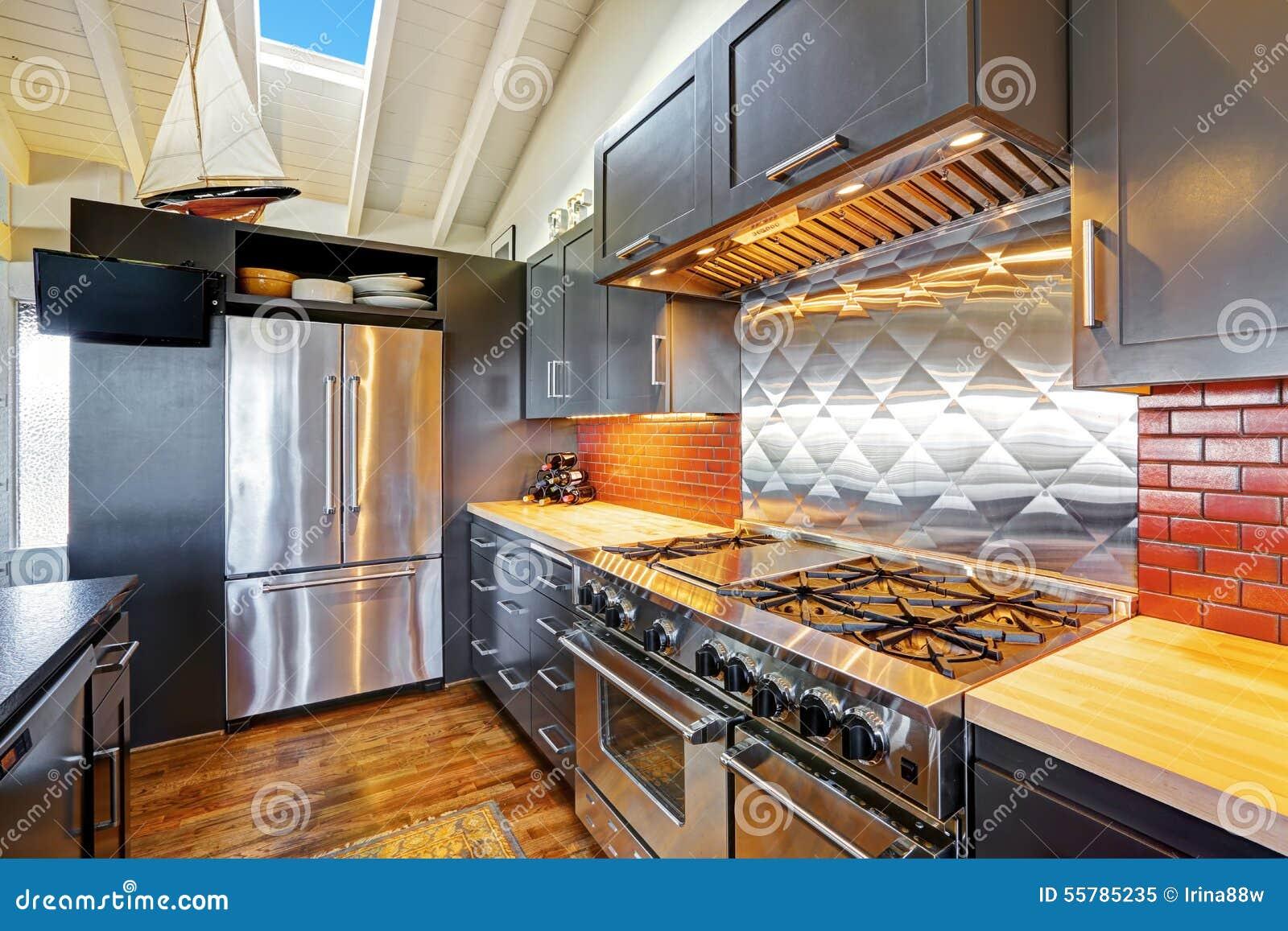Bella cucina moderna scura di lusso con il soffitto di legno arcato