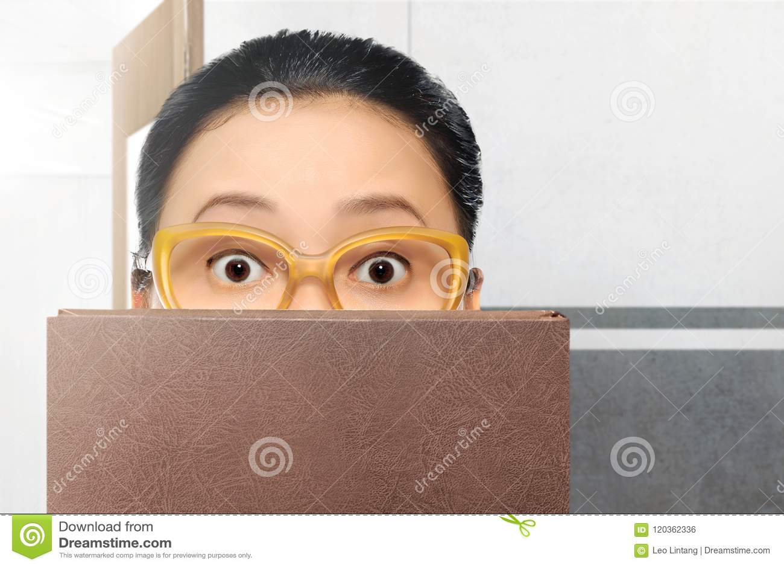 Bella donna asiatica dello studente con gli occhiali ed il libro