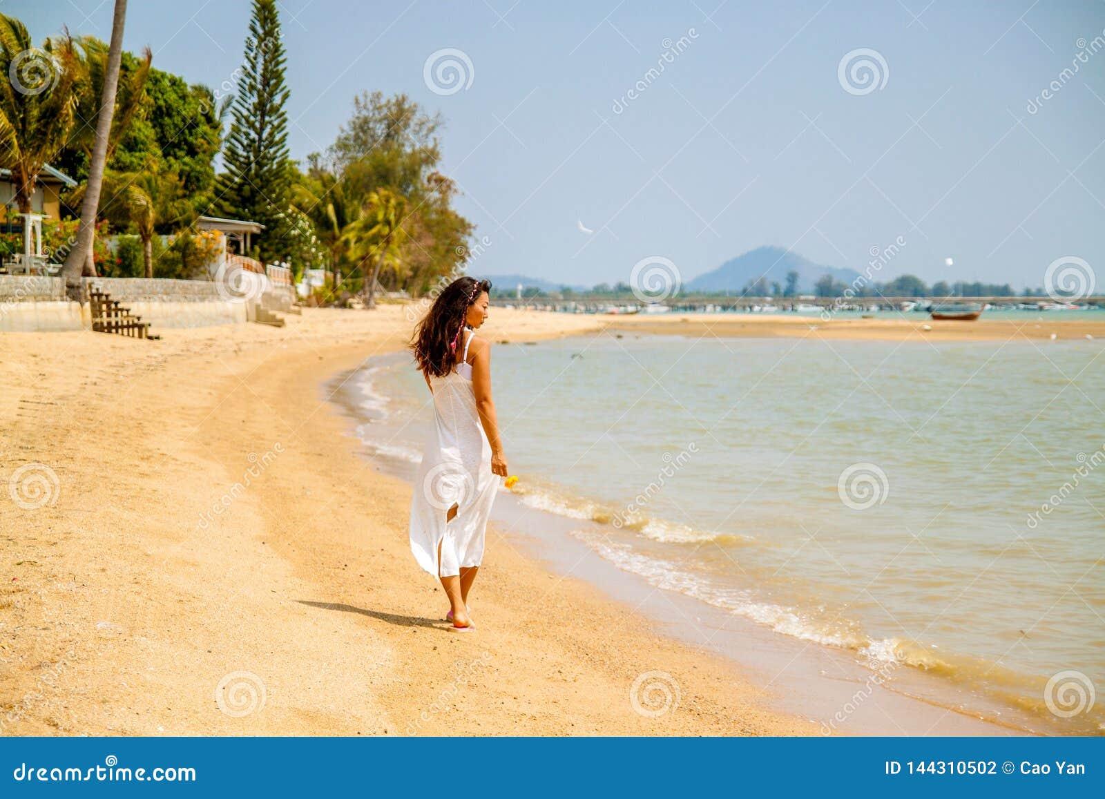 Bella donna asiatica nelle passeggiate bianche del vestito sulla spiaggia