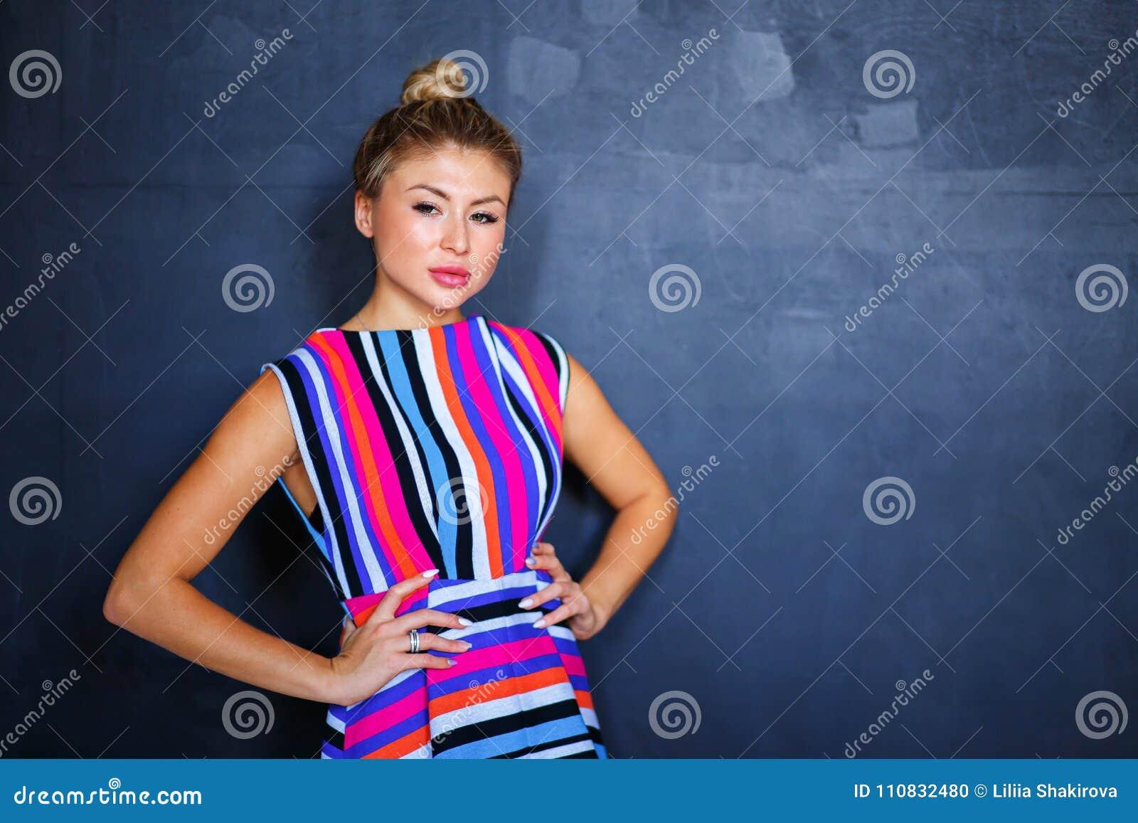 Bella donna bionda sexy su fondo grigio Ragazza sexy in vestito