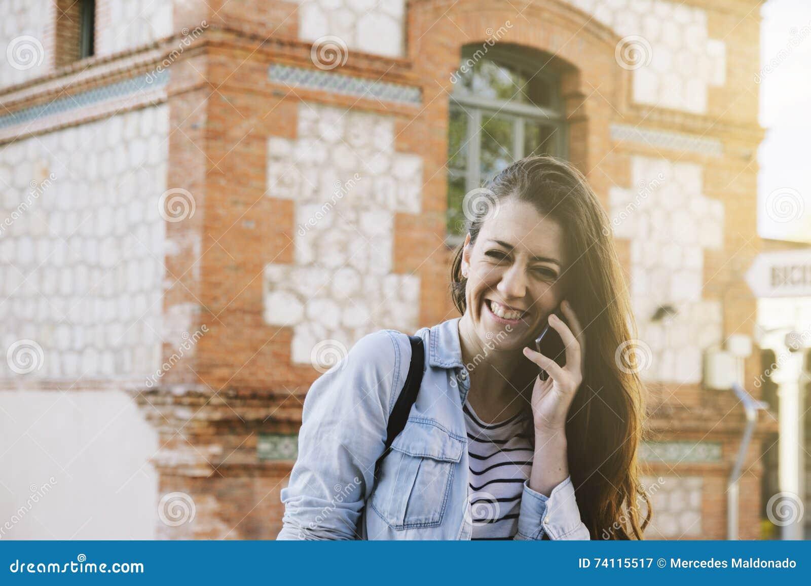 Bella donna castana che parla sul telefono