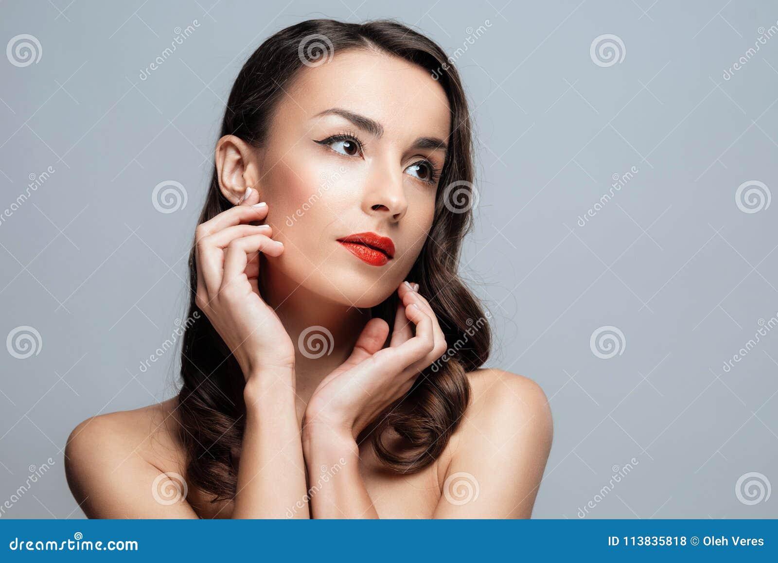 Bella donna castana con rossetto rosso sulle labbra Ragazza del primo piano con bello trucco