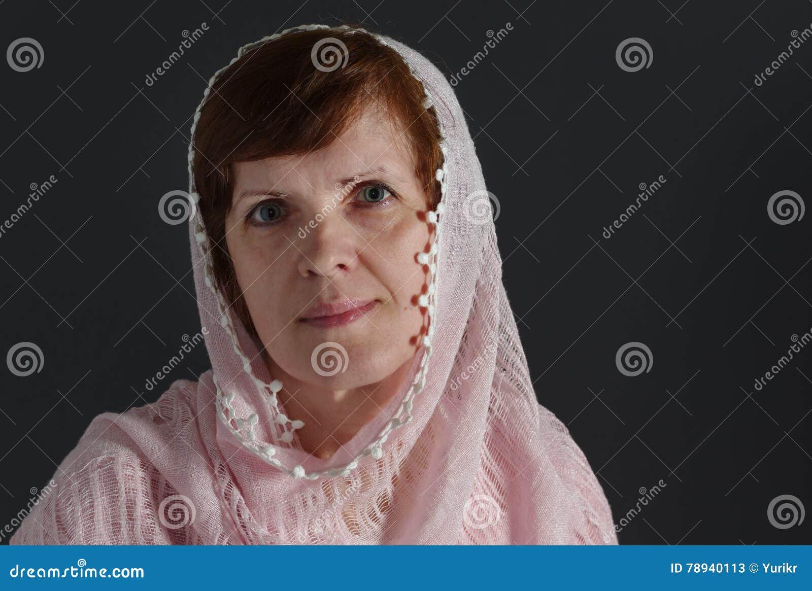 Bella donna caucasica matura che porta scialle color crema contro il fondo  scuro 116dc76f13cf