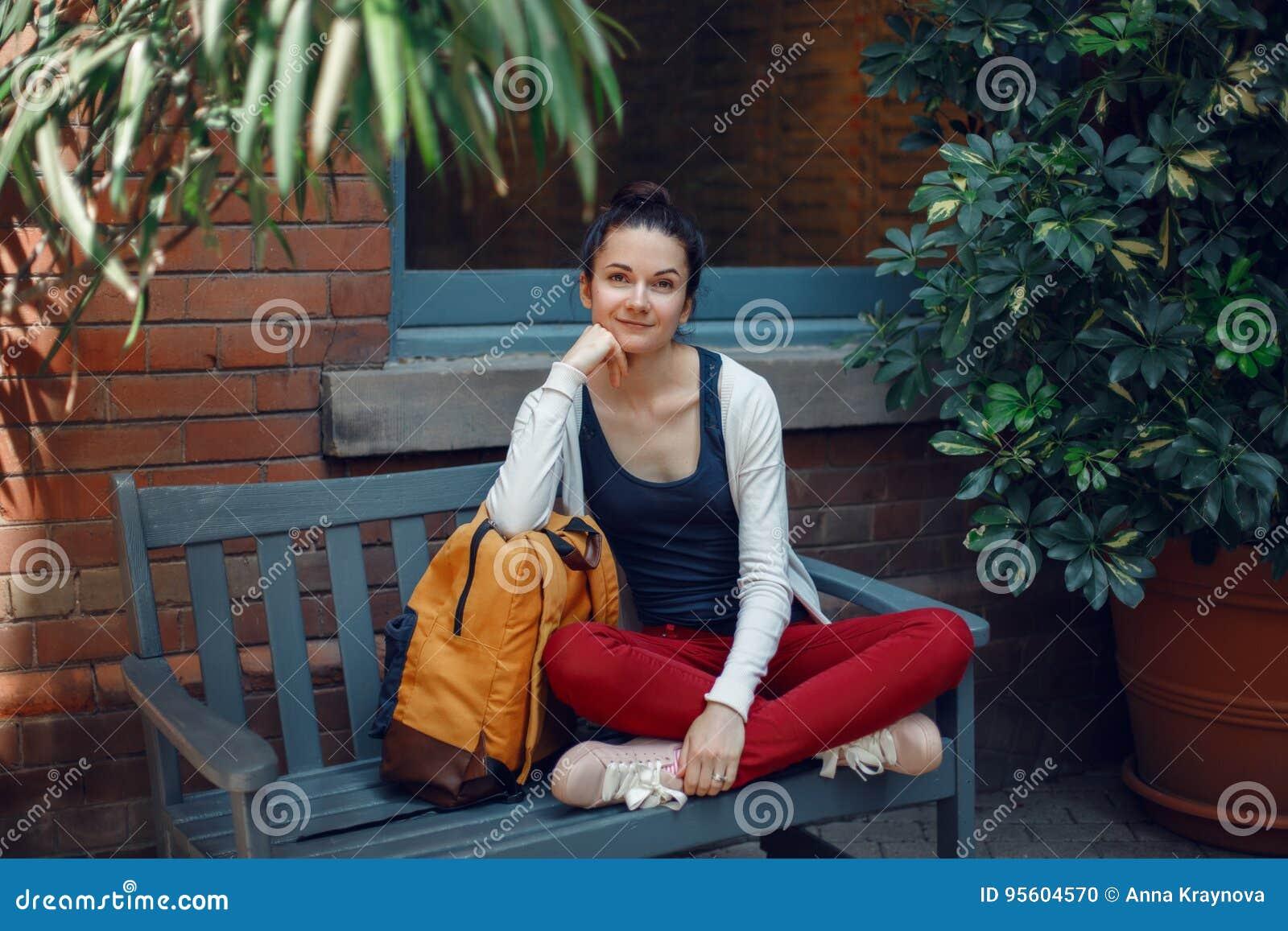 Bella donna caucasica sorridente della ragazza in maglione bianco e jeans rossi, sedentesi con lo zaino giallo della borsa di via