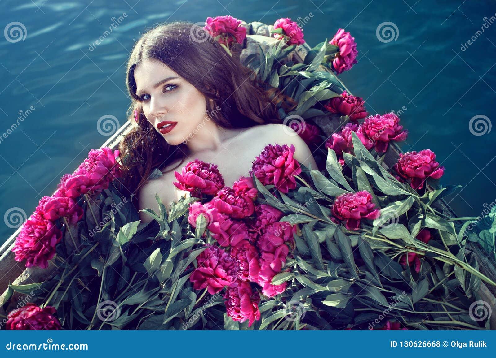 Bella donna che si trova nella barca di legno coperta di mucchio enorme delle peonie