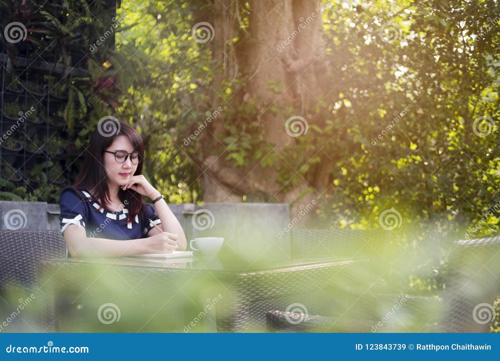 Bella donna che writeing sul libro su fondo teble e vago, b