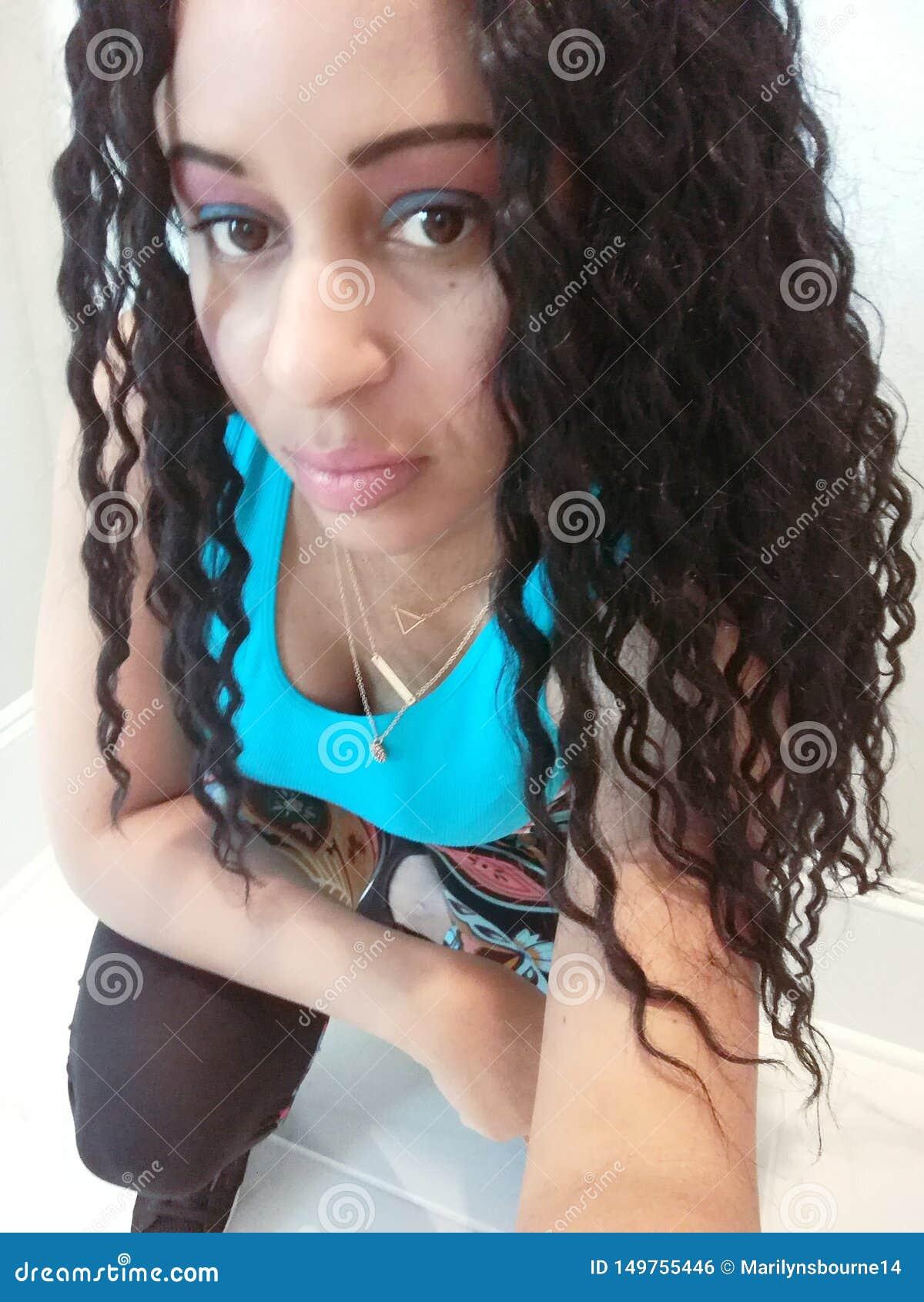 Bella donna con capelli ricci che si esercita in una cima blu