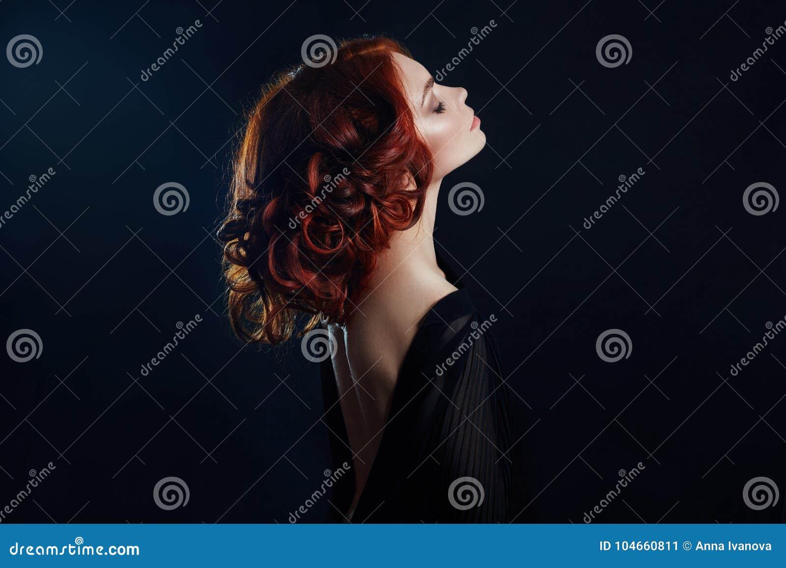 Bella donna con capelli rossi su un fondo nero Ritratto di riuscita donna, pelle pura, trucco naturale, fronte di cura di pelle
