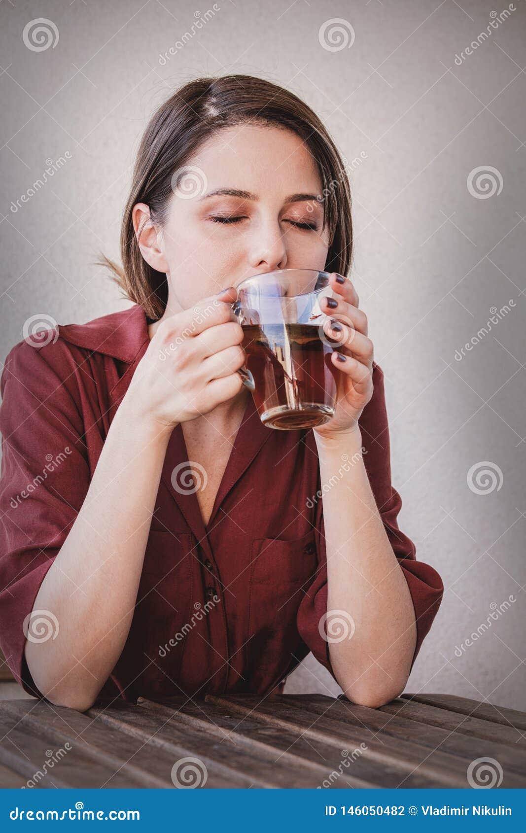 Bella donna con la tazza di t? a casa in una mattina