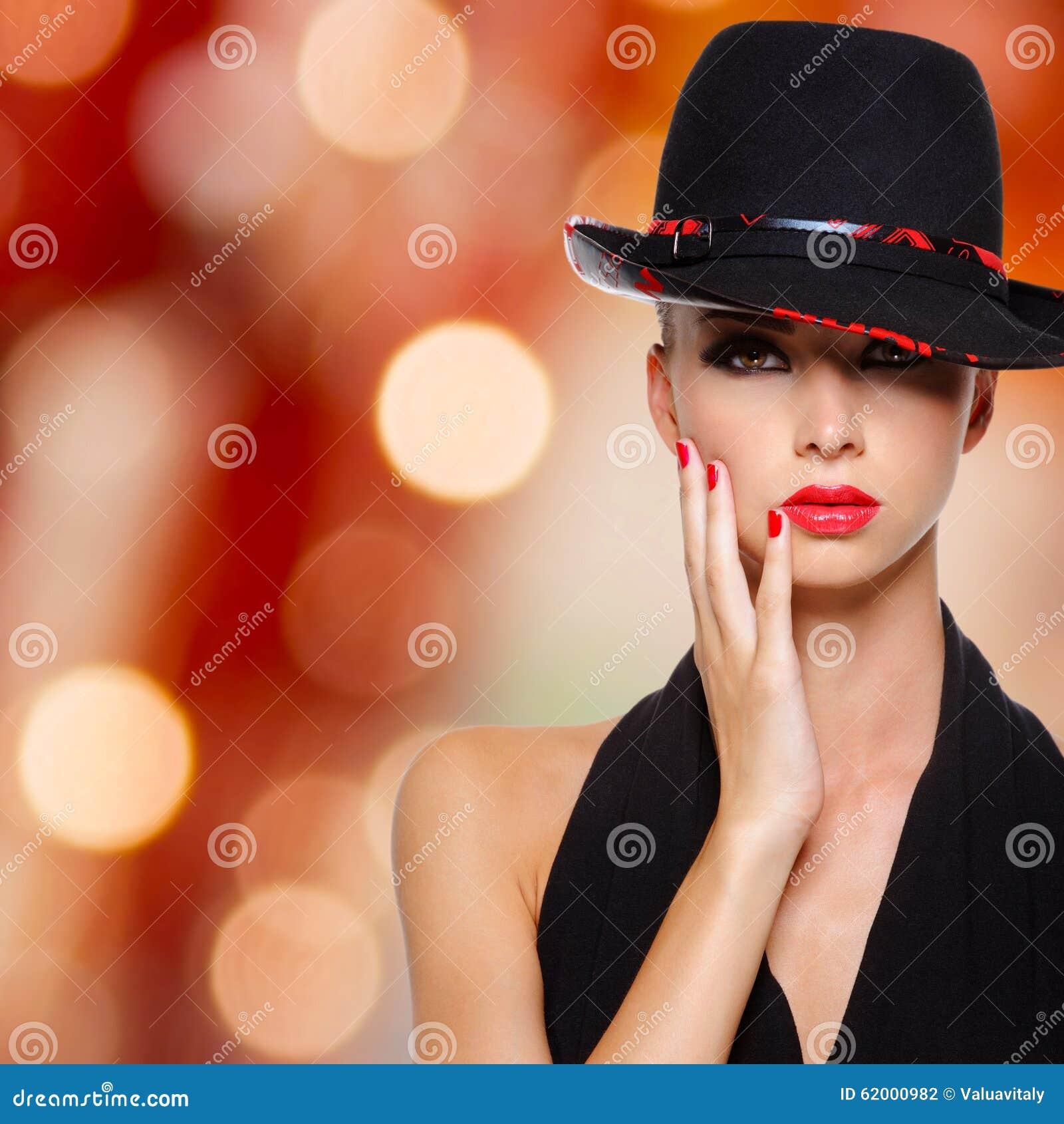 Bella donna con le labbra ed i chiodi rossi in black hat