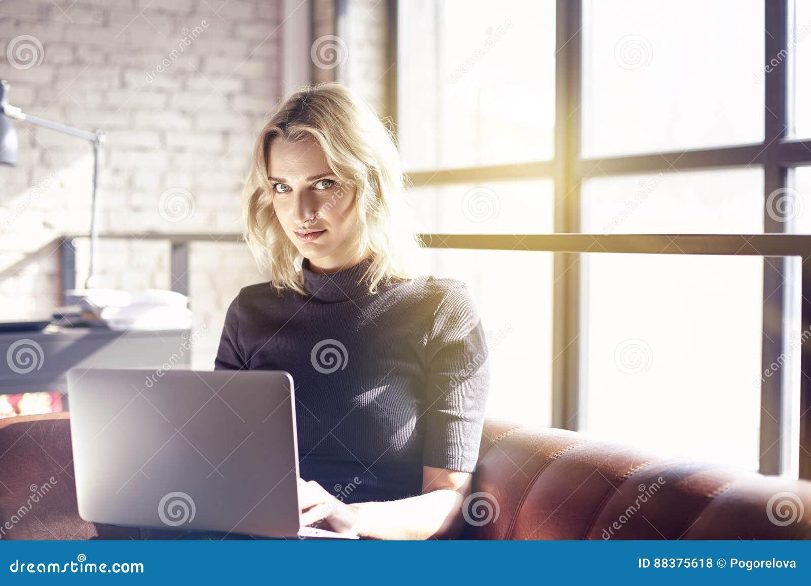 Bella donna di affari bionda che si siede nell ufficio soleggiato che lavora al computer portatile Concetto dei dispositivi mobil