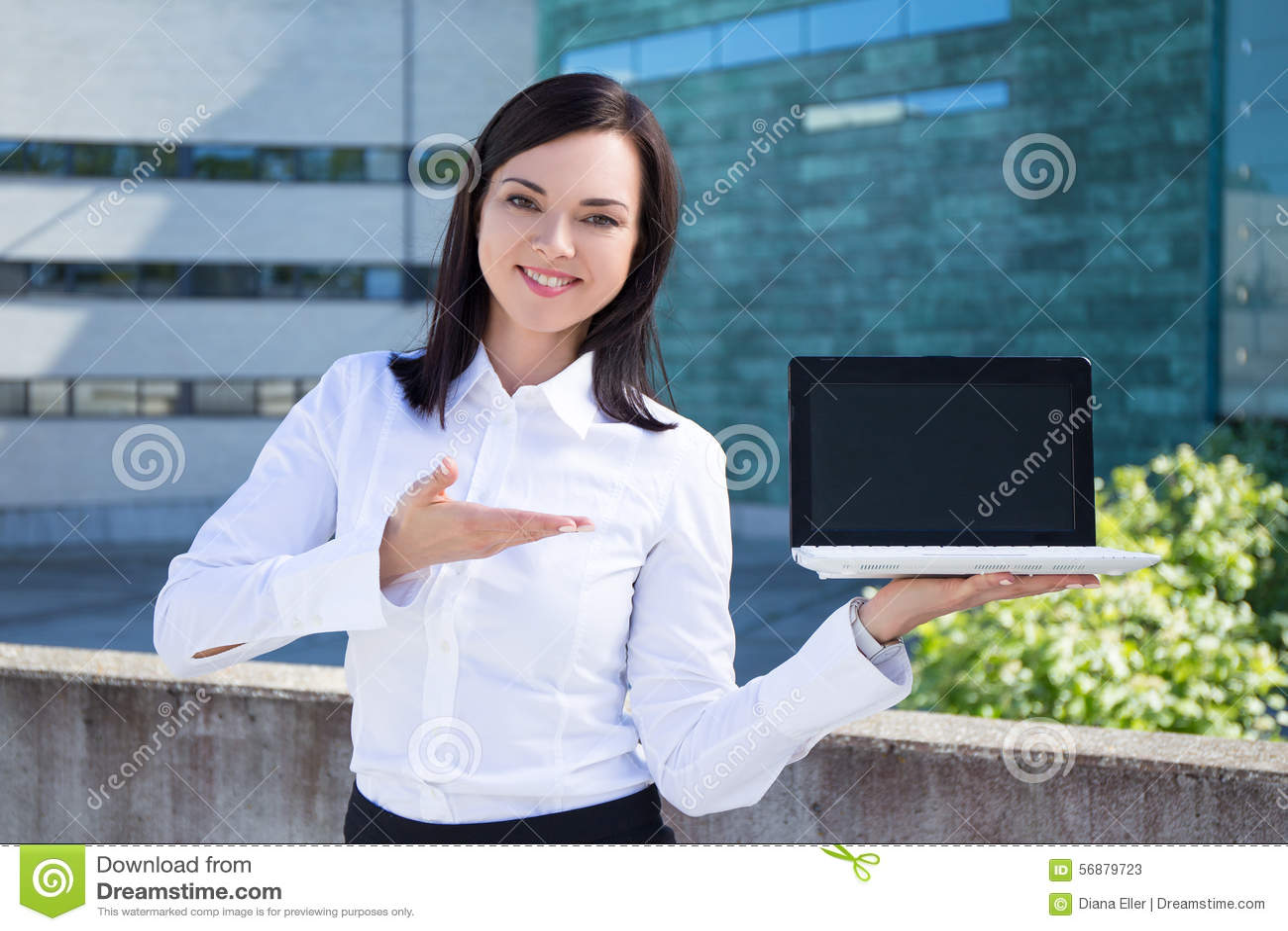 Bella donna di affari che mostra computer portatile con lo schermo in bianco