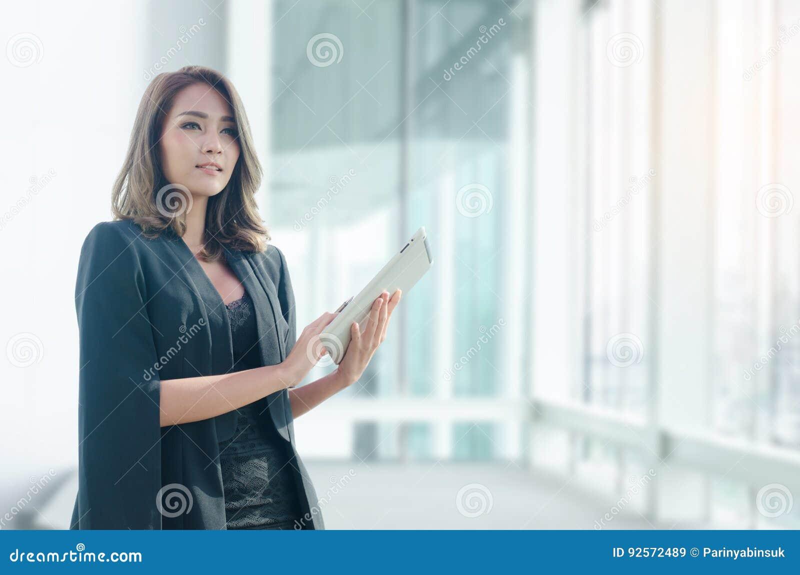 Bella donna di affari che utilizza compressa nell ufficio