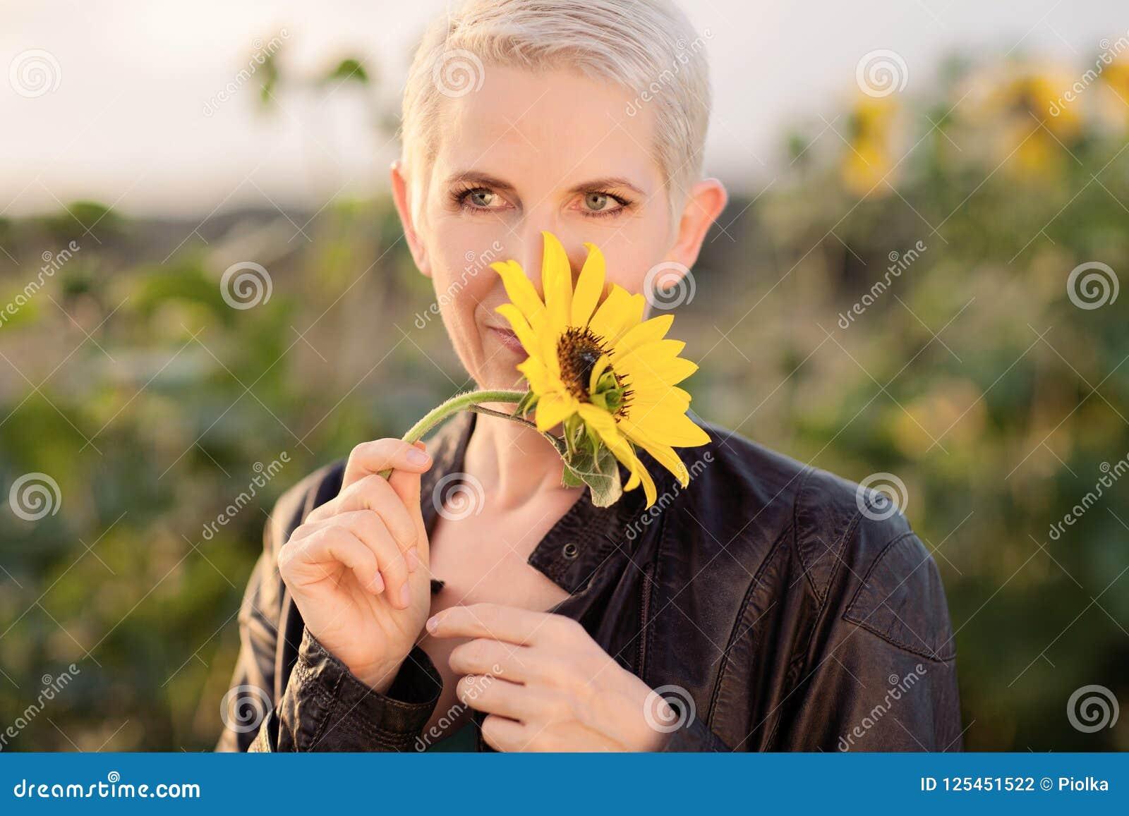 Bella donna di medio evo in una scena rurale del campo all aperto che sta fra i girasoli