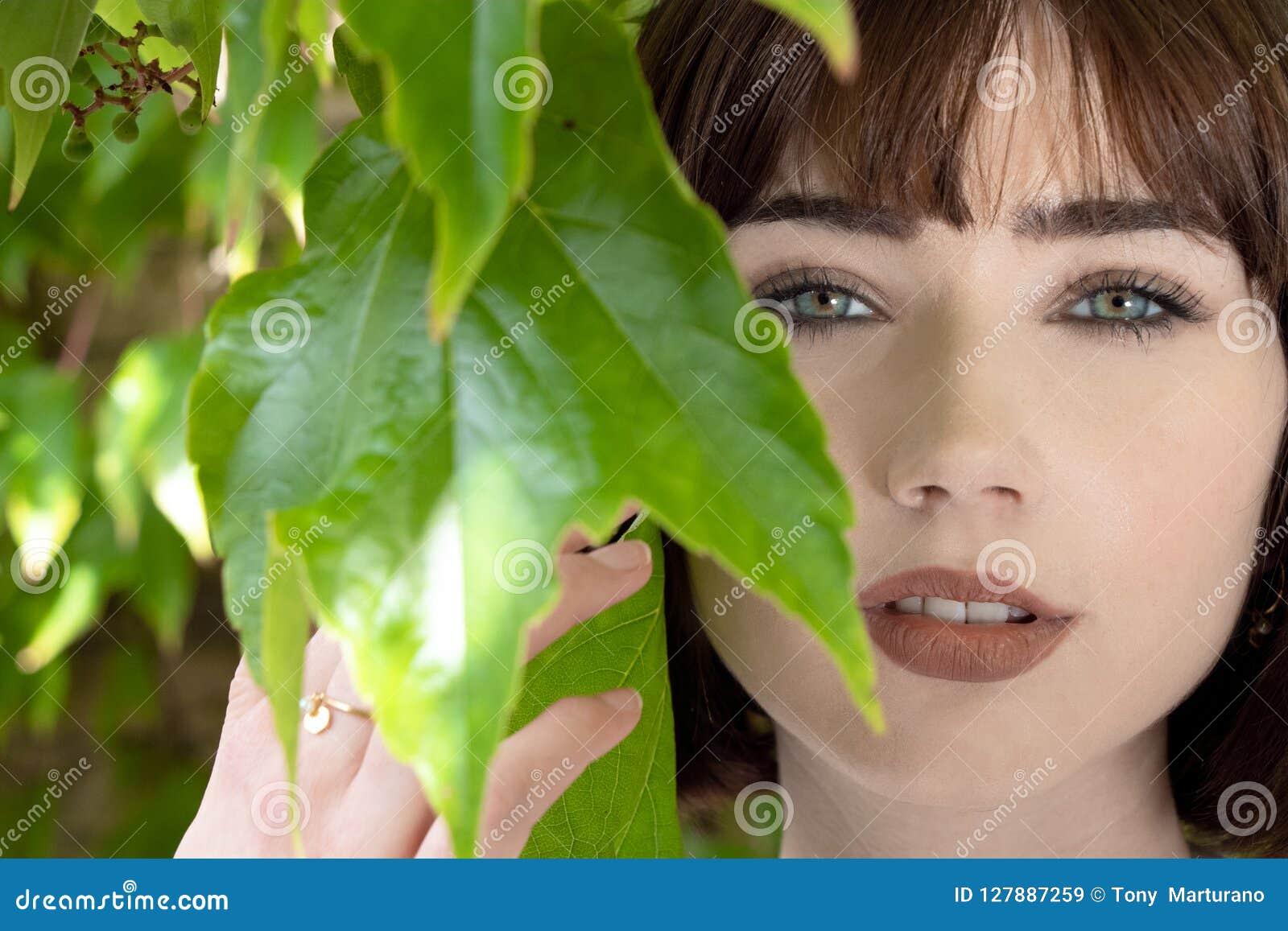 Bella donna dietro le foglie verdi che esaminano macchina fotografica