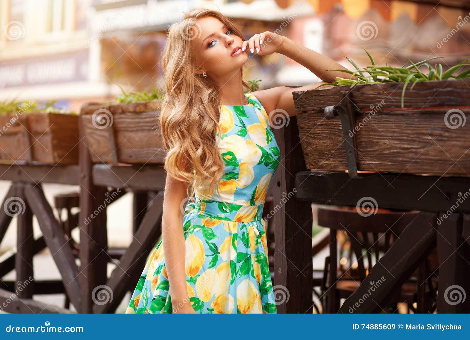 Bella donna elegante in vestito romantico sopra il caffè con i fiori