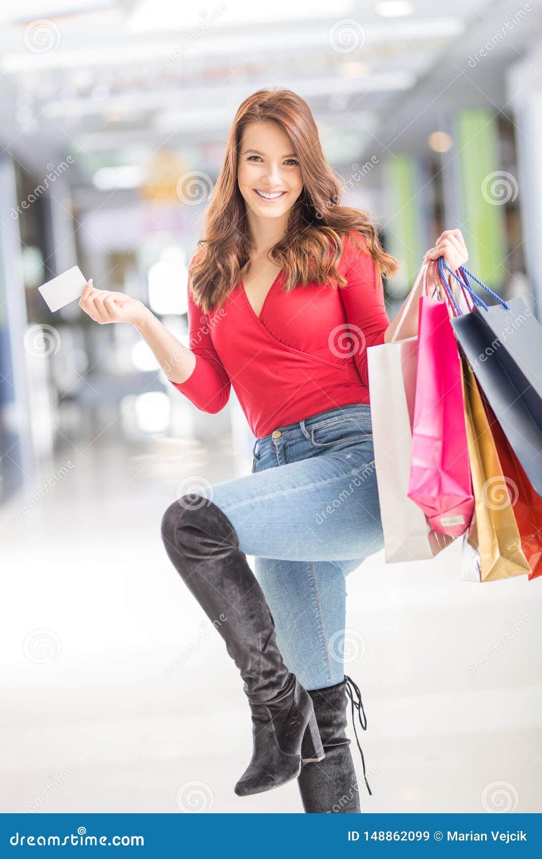 Bella donna felice con la carta di credito e sacchetti della spesa nel centro commerciale