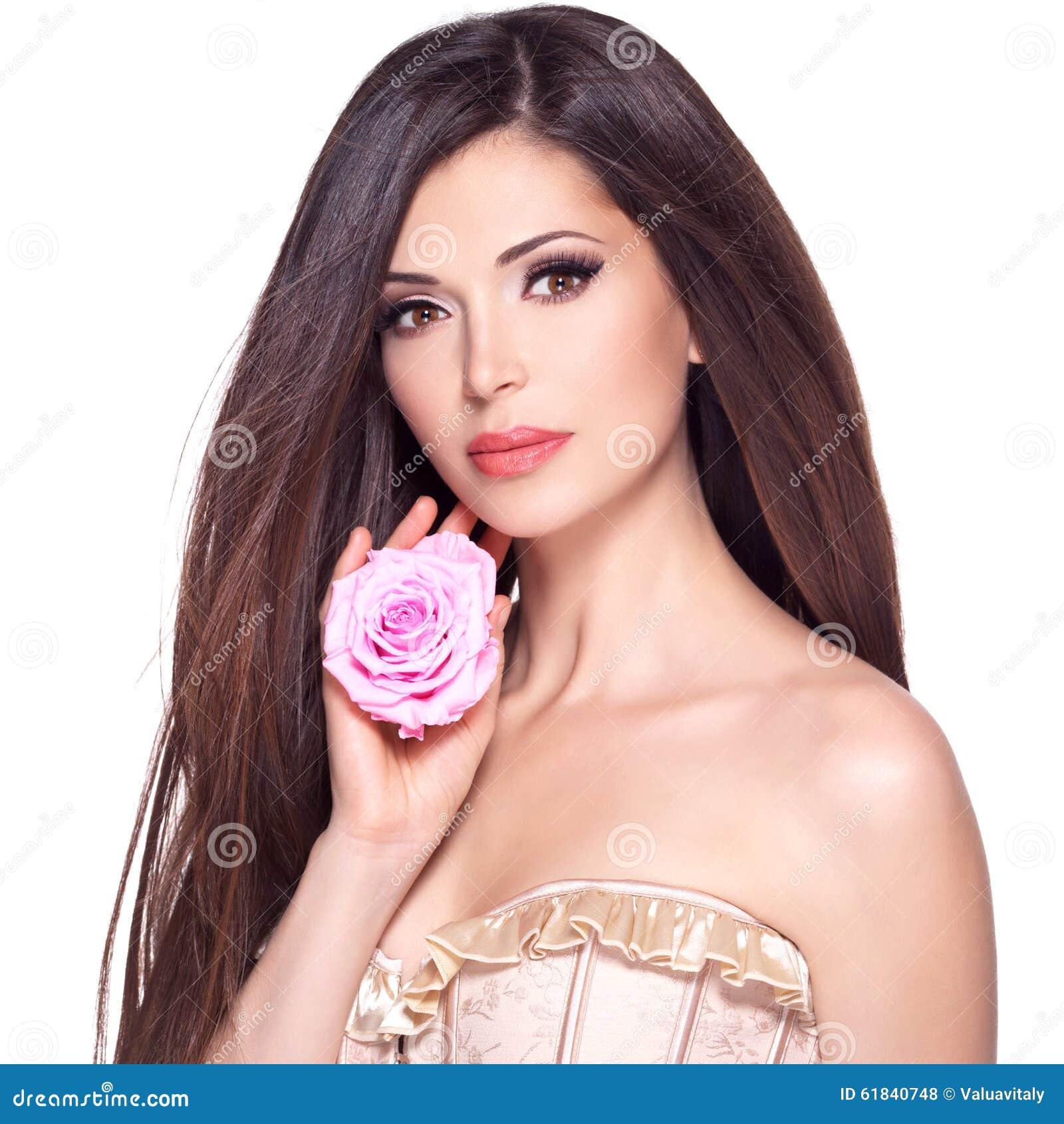 Bella donna graziosa con la rosa lunga di rosa e dei capelli al fronte