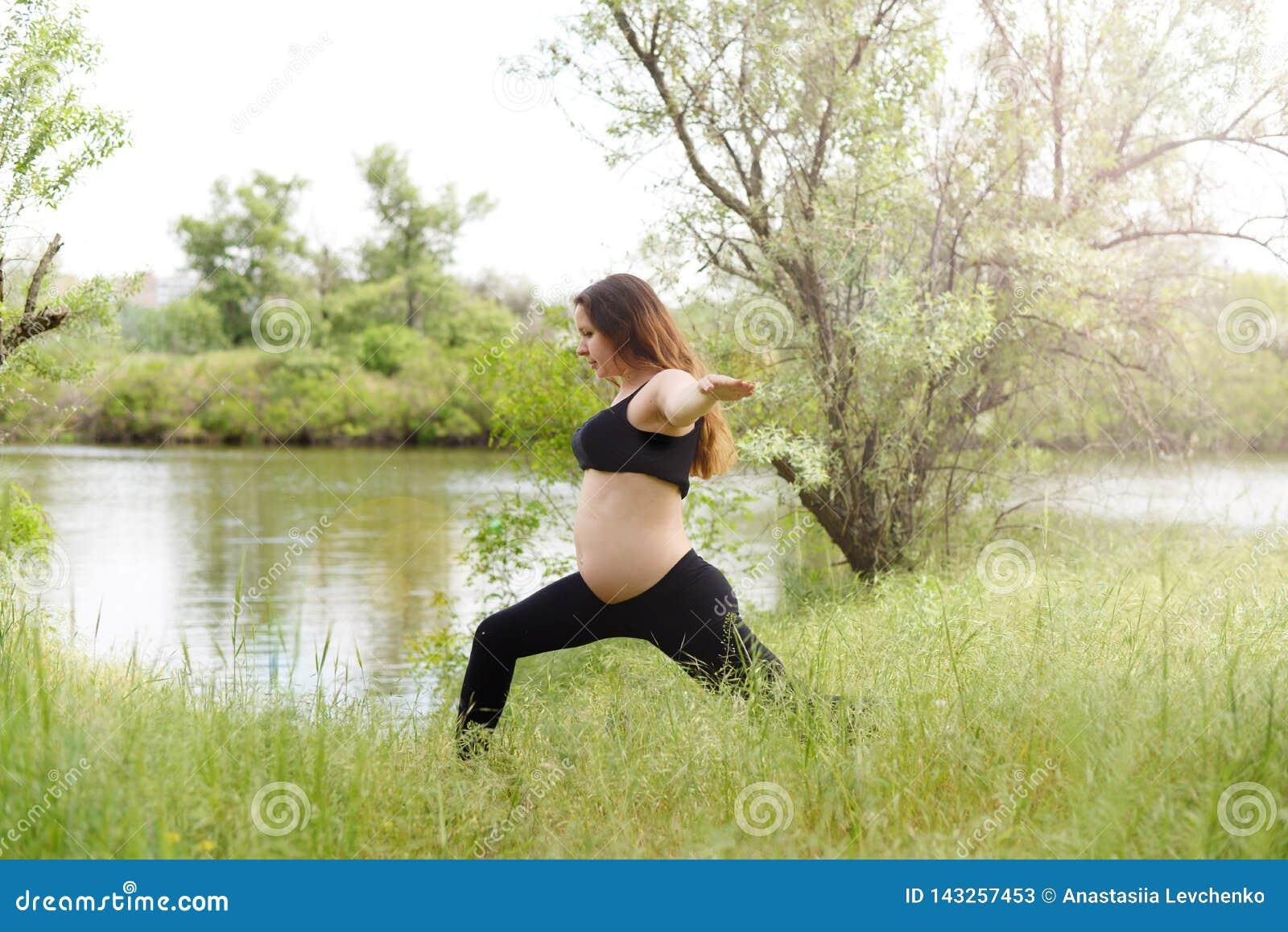 Bella donna incinta che fa yoga prenatale sulla natura all aperto Sport, forma fisica, stile di vita sano mentre gravidanza Donna