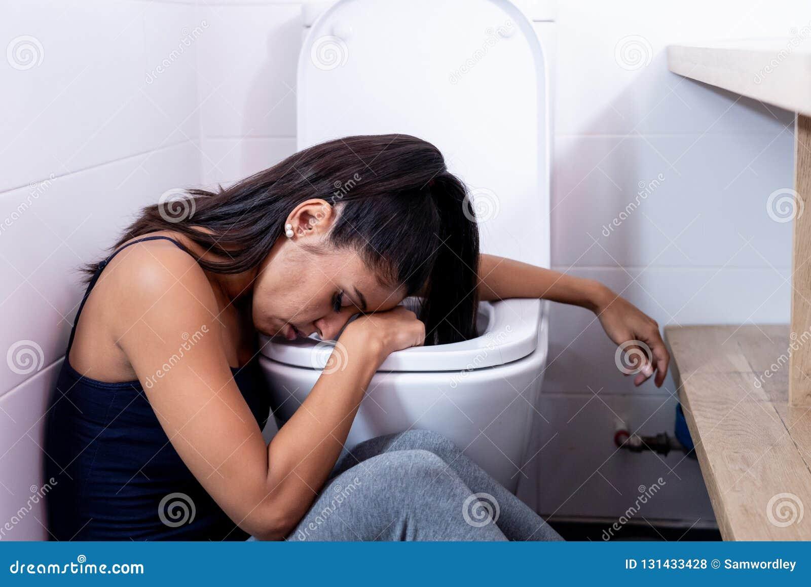 Bella donna latina che si siede nel bagno che soffre dalla bulimia di anoressia che ritiene triste e colpevole disperati nei diso