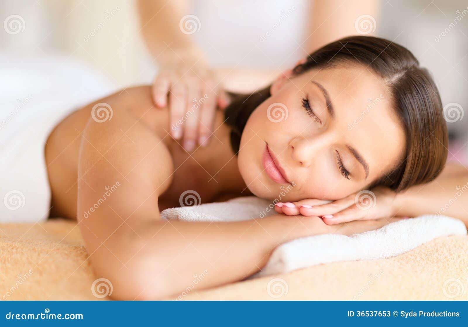 Bella donna nel salone della stazione termale che ottiene massaggio