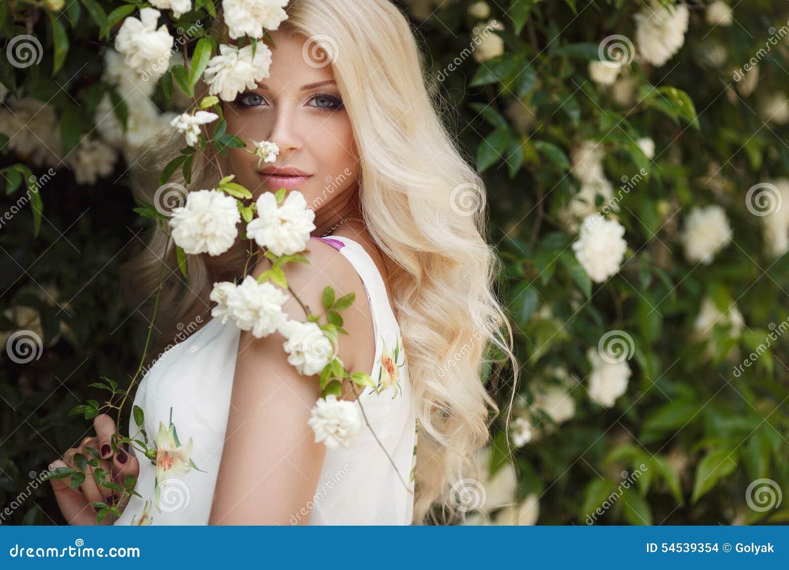 Bella donna in parco vicino alle rose di fioritura di Bush