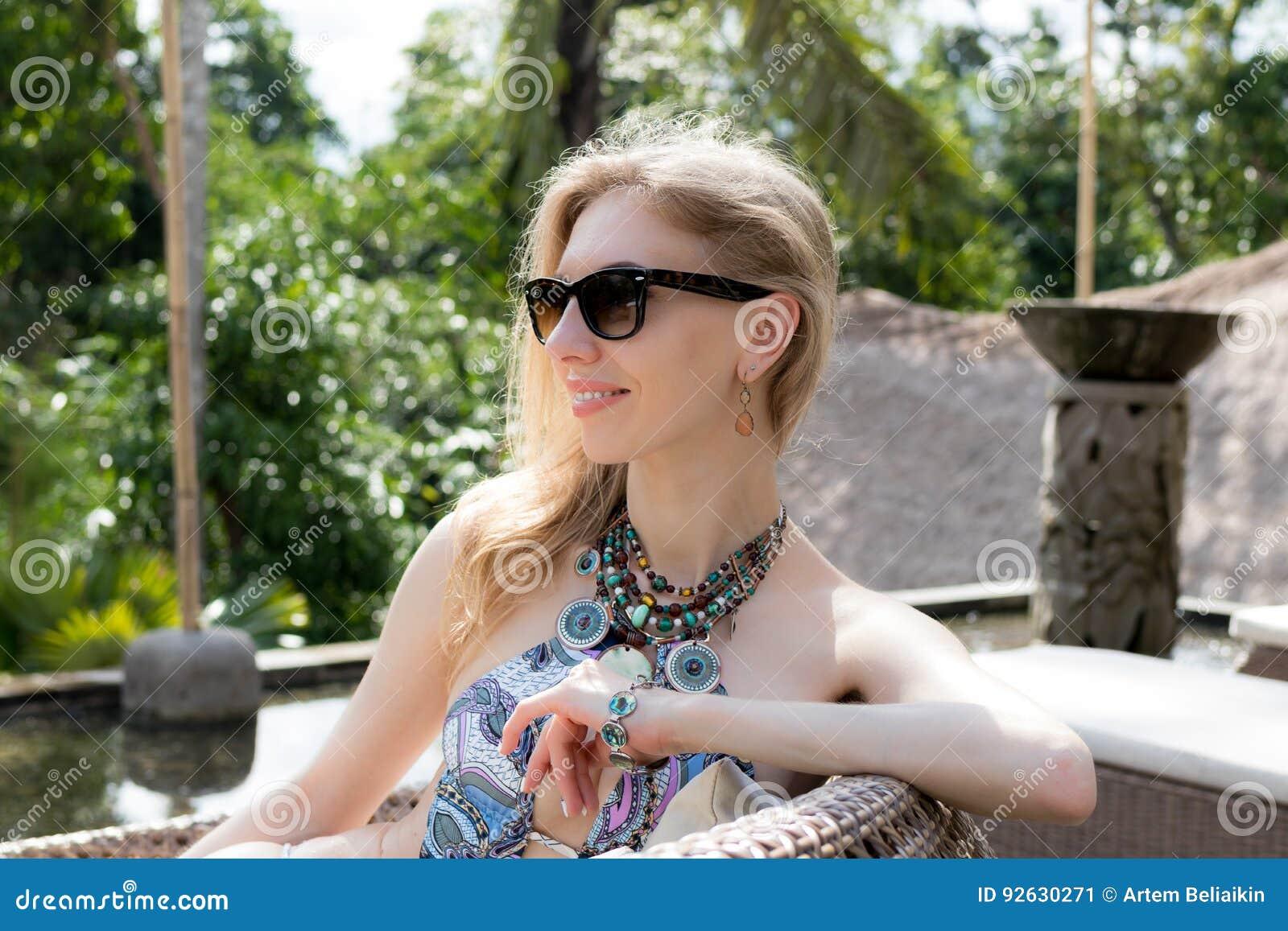 Bella donna sexy che prende il sole nella piscina Modello di lusso allo stagno