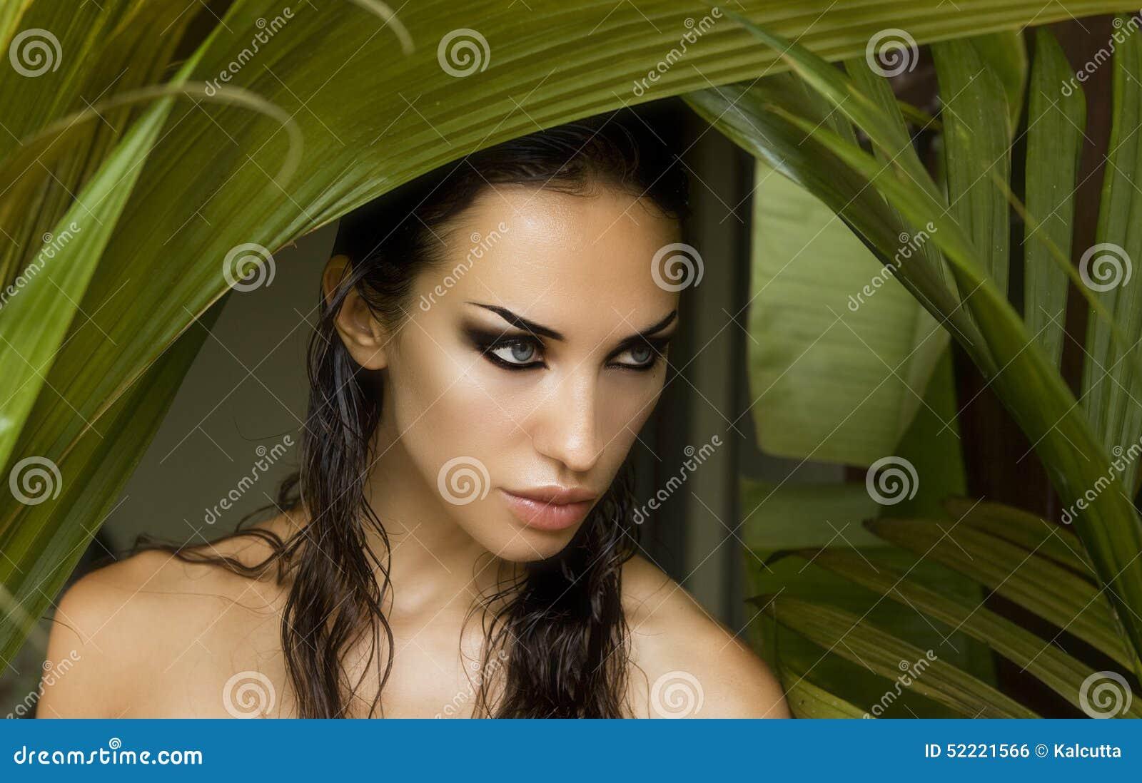 Bella donna sexy che si nasconde dietro le foglie di palma