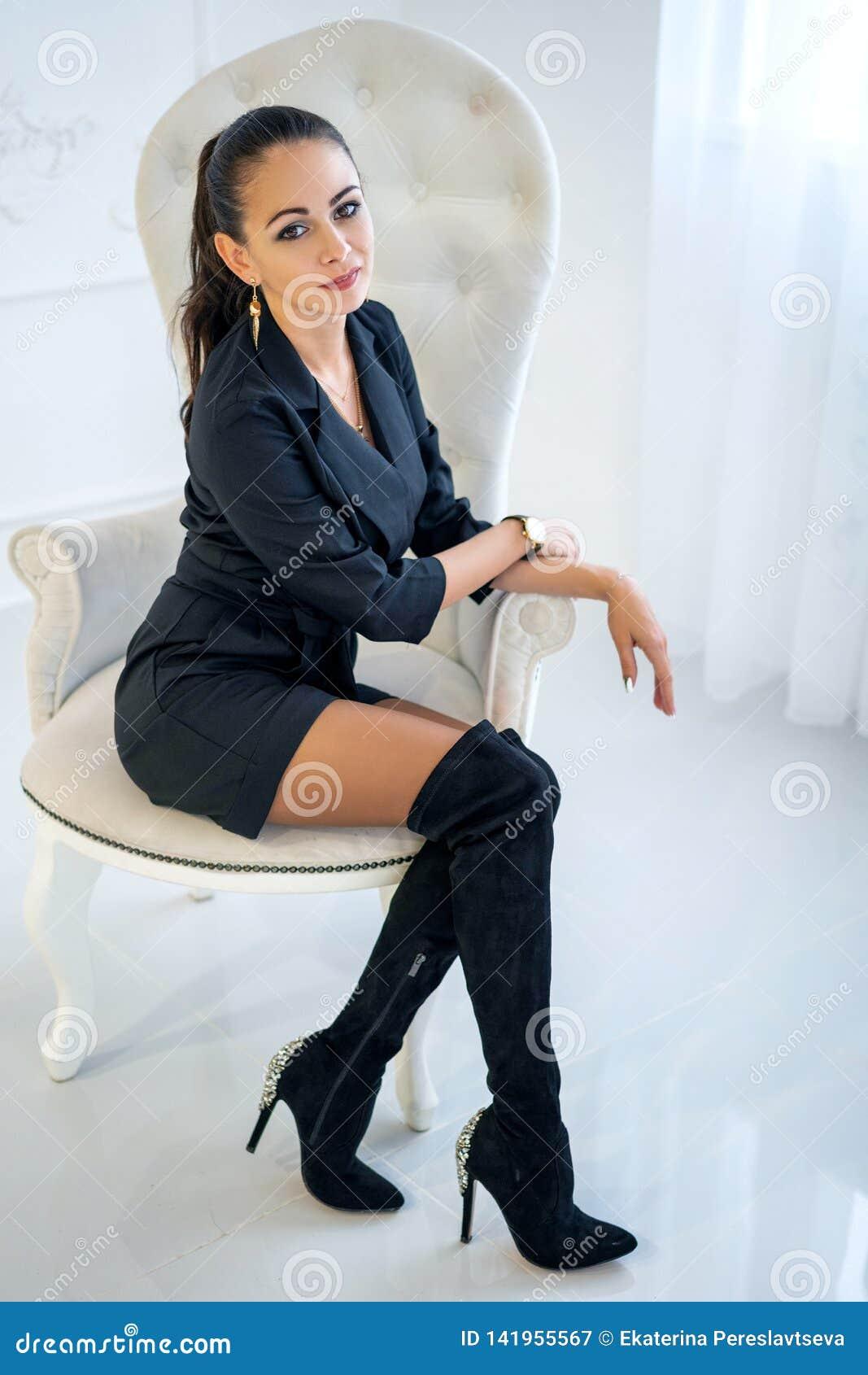 Bella donna sicura alla moda che si siede in una sedia bianca nello studio