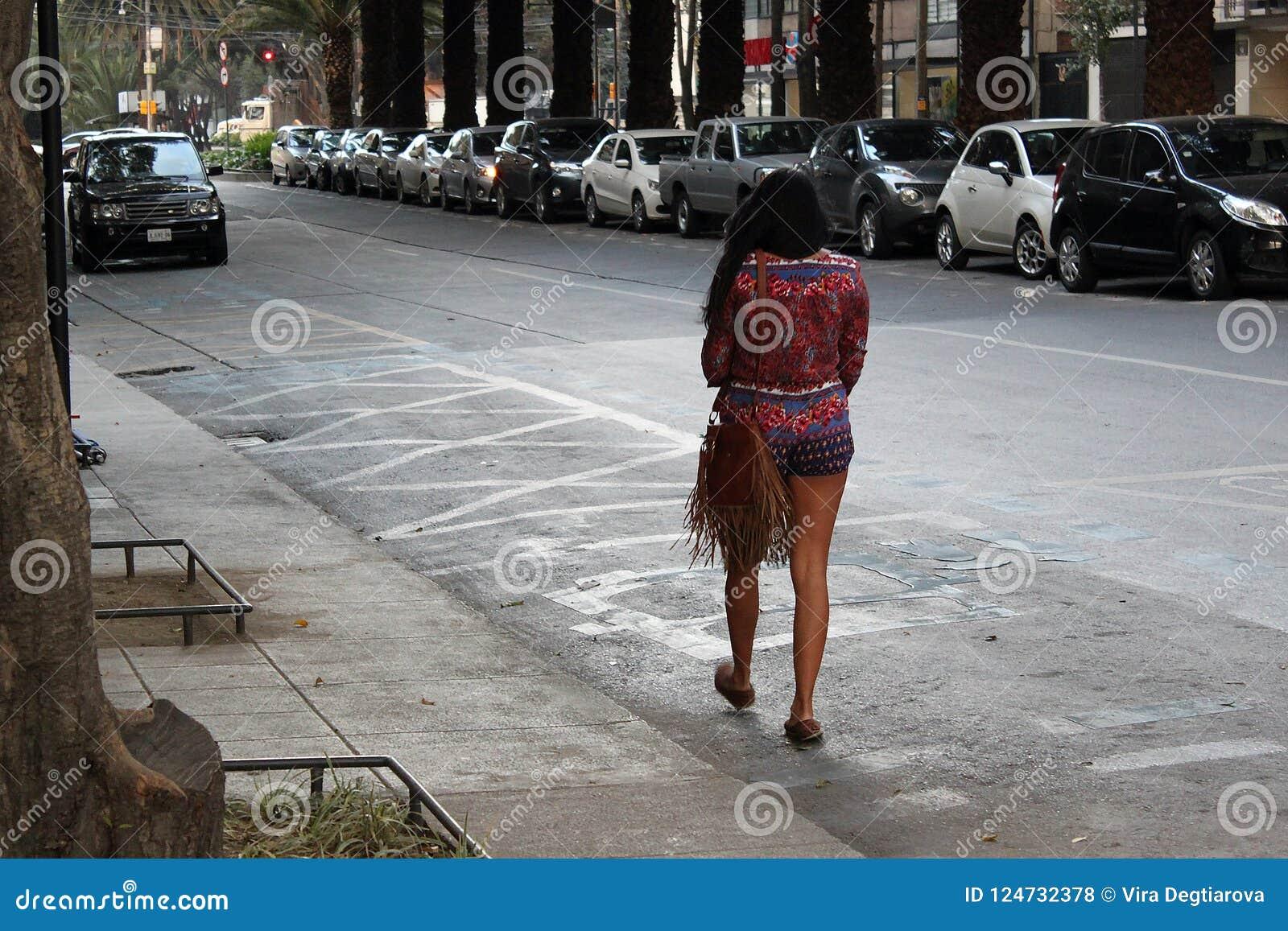 Bella donna sola che cammina sulla via