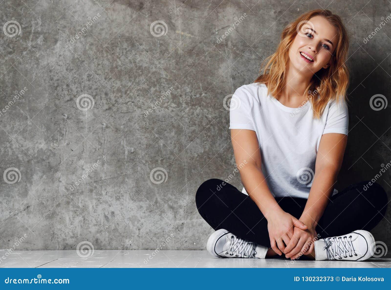 Bella donna sorridente che si siede sul pavimento contro il muro di cemento