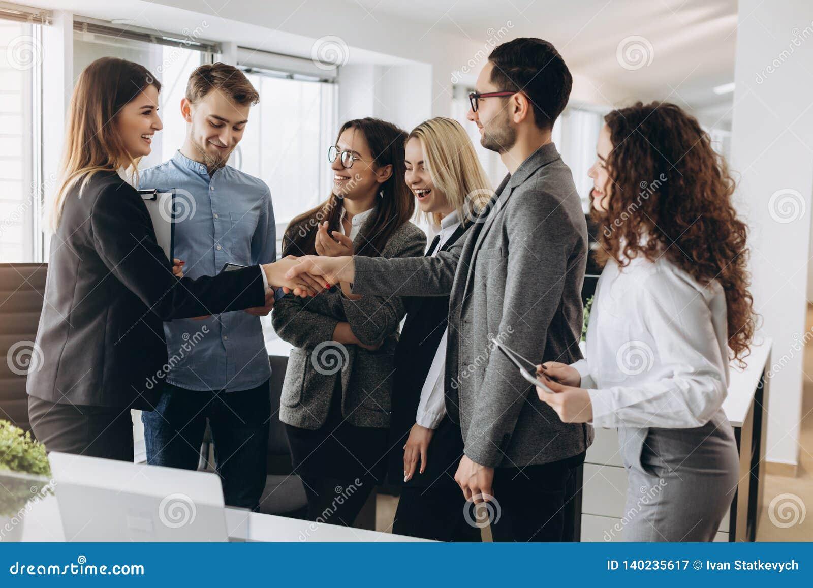 Bella donna sorridente che stringe mano maschio, accogliente stretta di mano del richiedente femminile che arriva all intervista