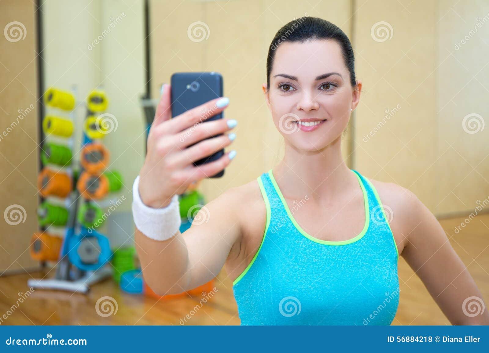 Bella donna sportiva che fa la foto del selfie sullo smartphone in palestra