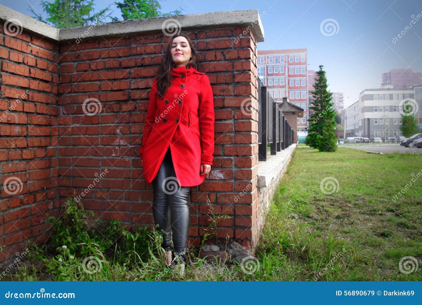 Bella donna in un cappotto rosso su un muro di mattoni nella città
