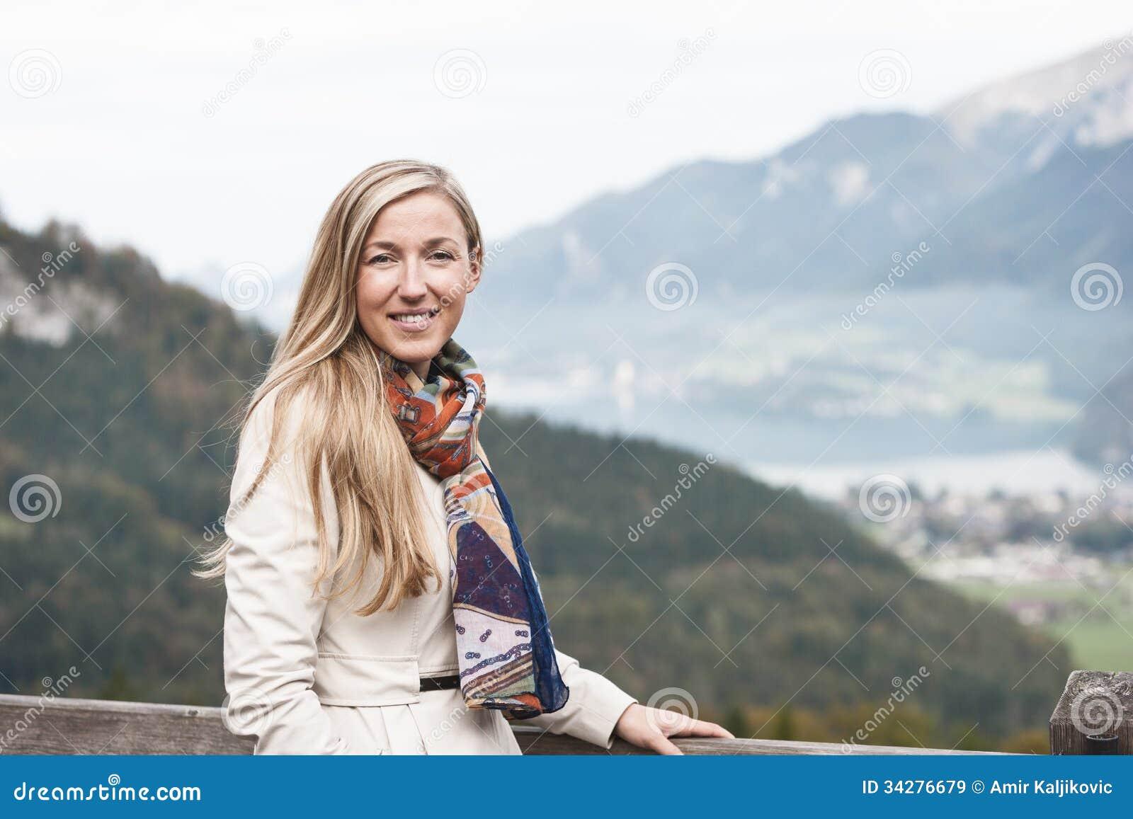 Bella donna in un impermeabile ed in una sciarpa
