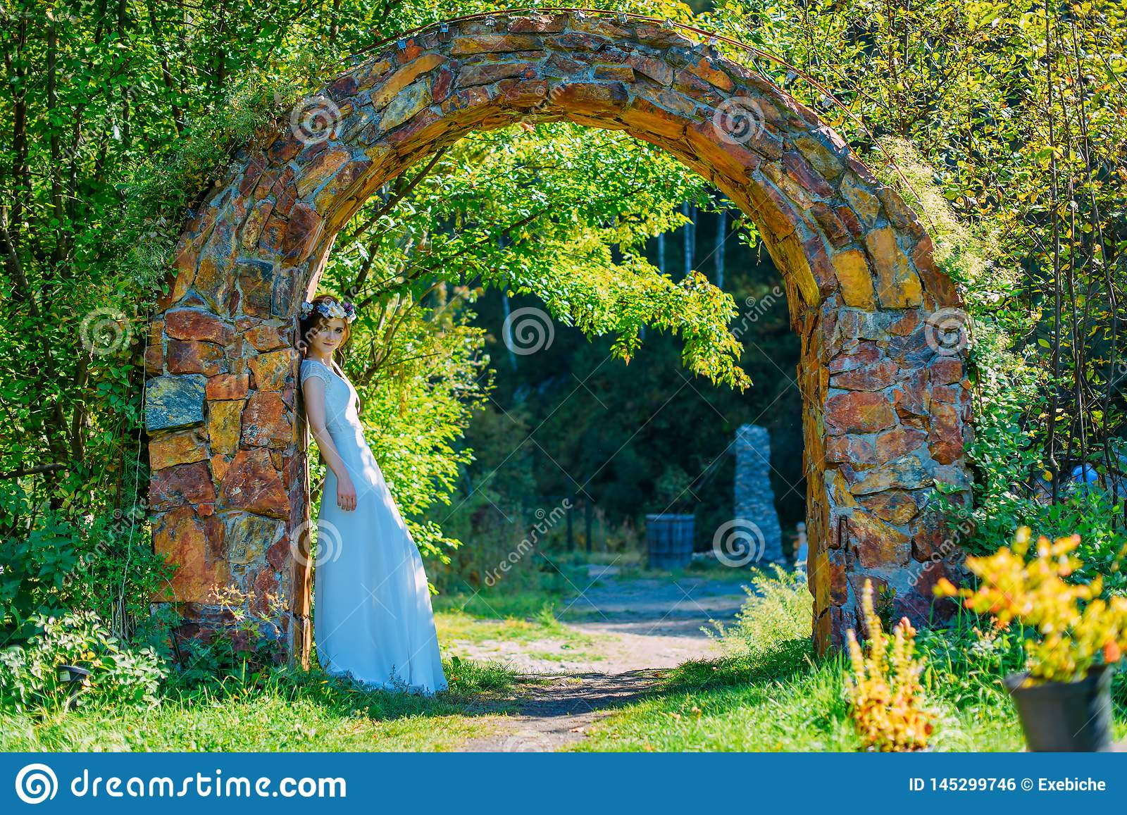 Bella e giovane sposa in vestito e cerchietto bianchi dei fiori che posano nell arco di pietra