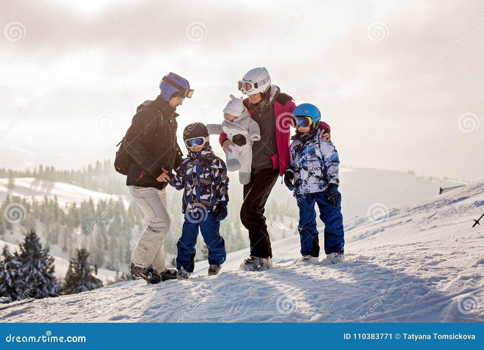 Bella famiglia con i bambini, scianti in un area di paesaggio in austriaco
